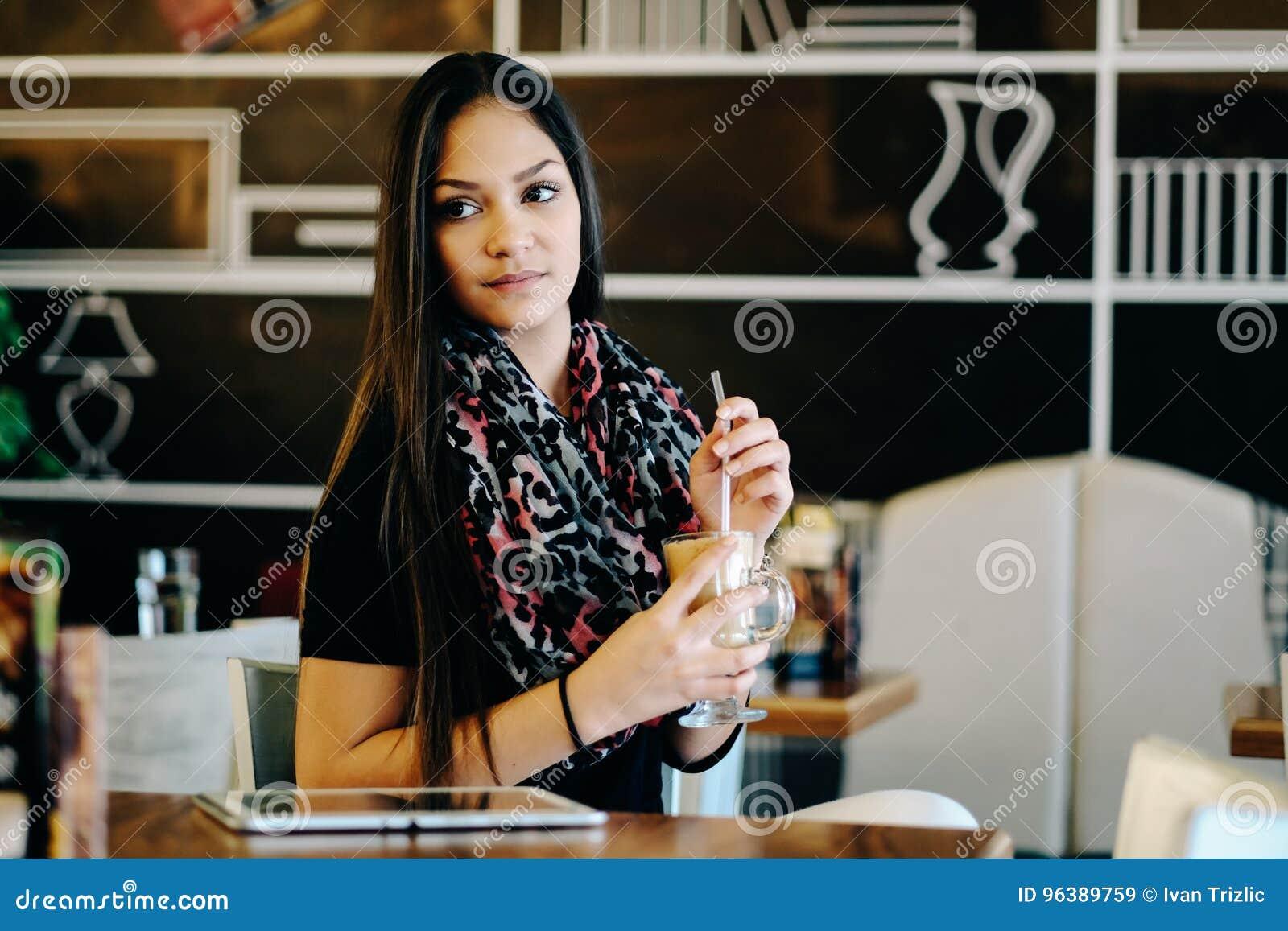 美丽的在咖啡馆的女孩饮用的冰上等咖啡震动