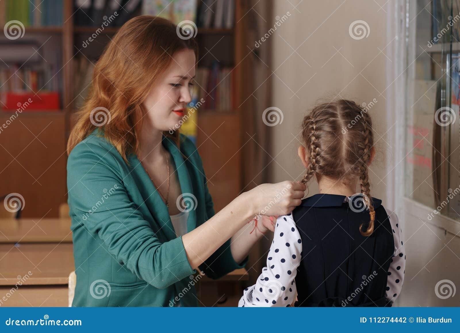 美丽的在家学习女孩和她的年轻的母亲一起读书或
