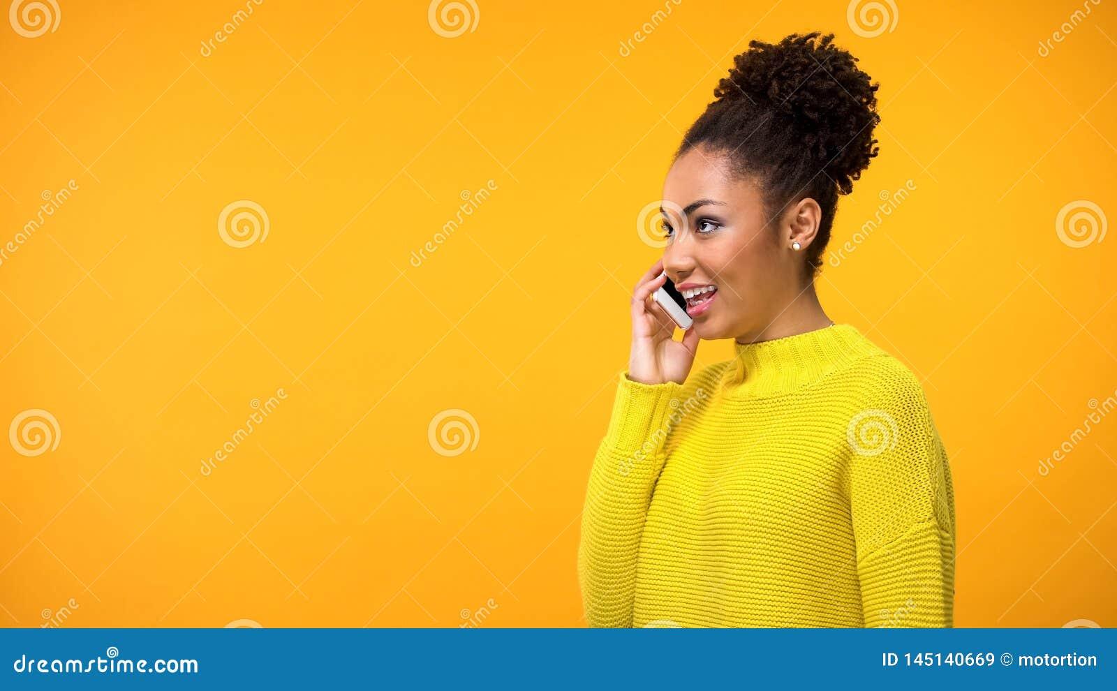 美丽的在橙色背景,交谈的年轻女人谈的智能手机