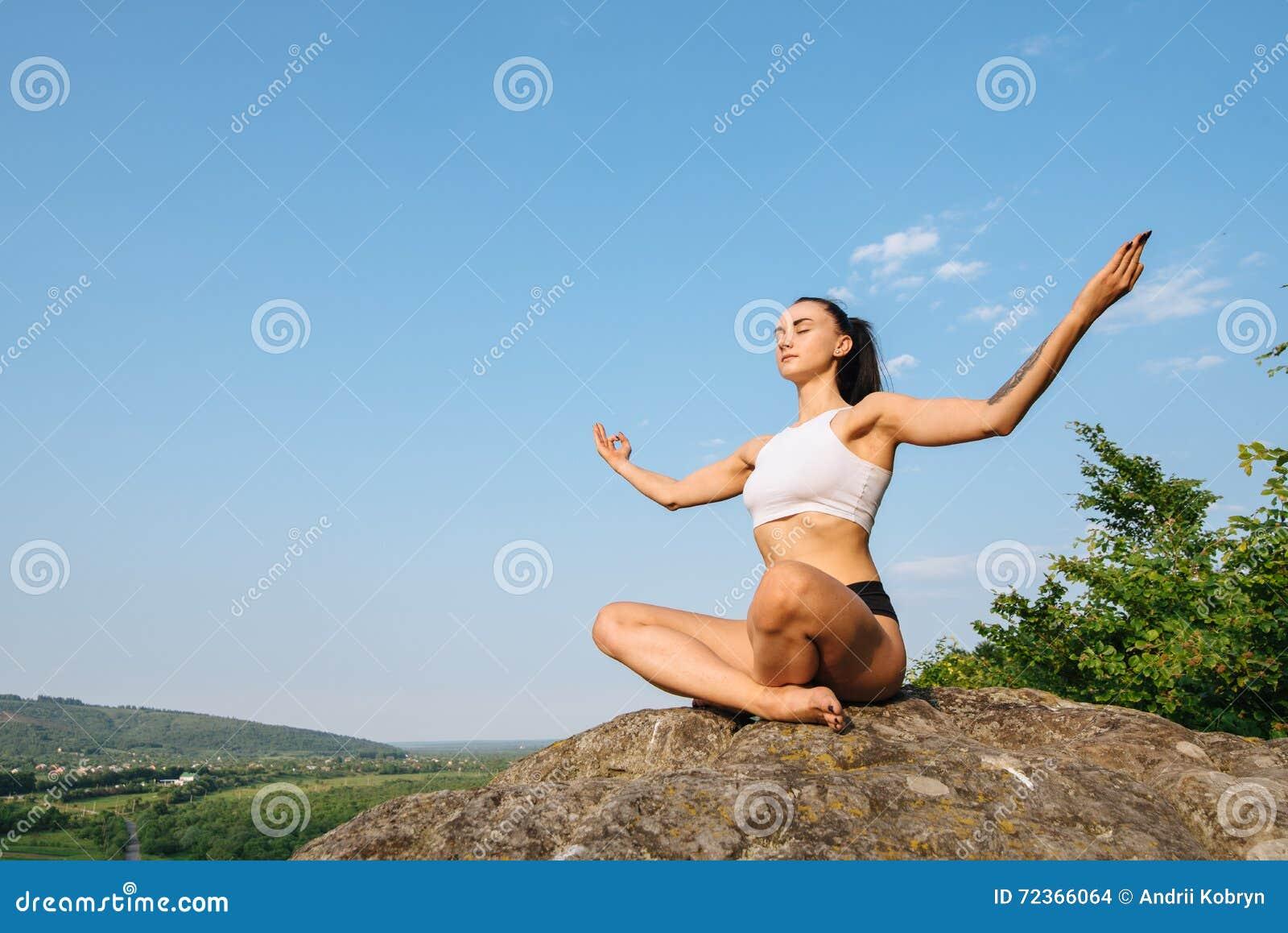 美丽的坚强的深色的在峭壁和放松边缘的女子实践的瑜伽
