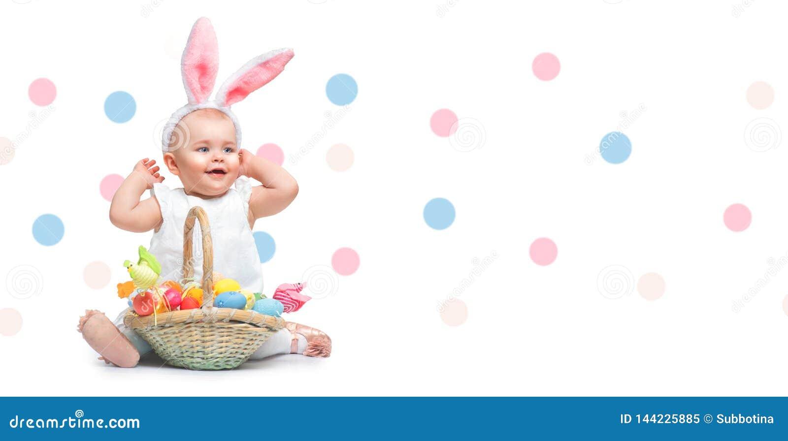 美丽的复活节微笑的女孩佩带的兔宝宝兔子耳朵,有篮子的充分五颜六色的被绘的复活节彩蛋