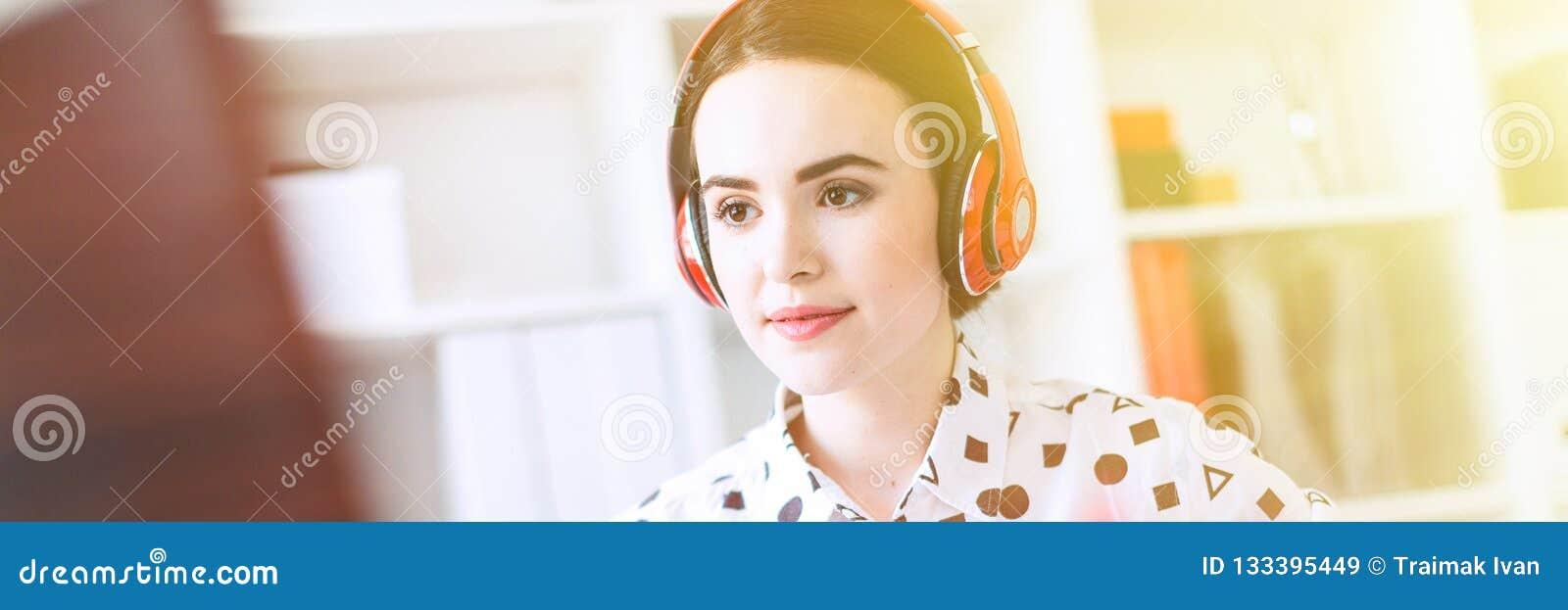美丽的女孩在耳机在键盘在她的手上坐在书桌在办公室,拿着一个笔记本并且打印