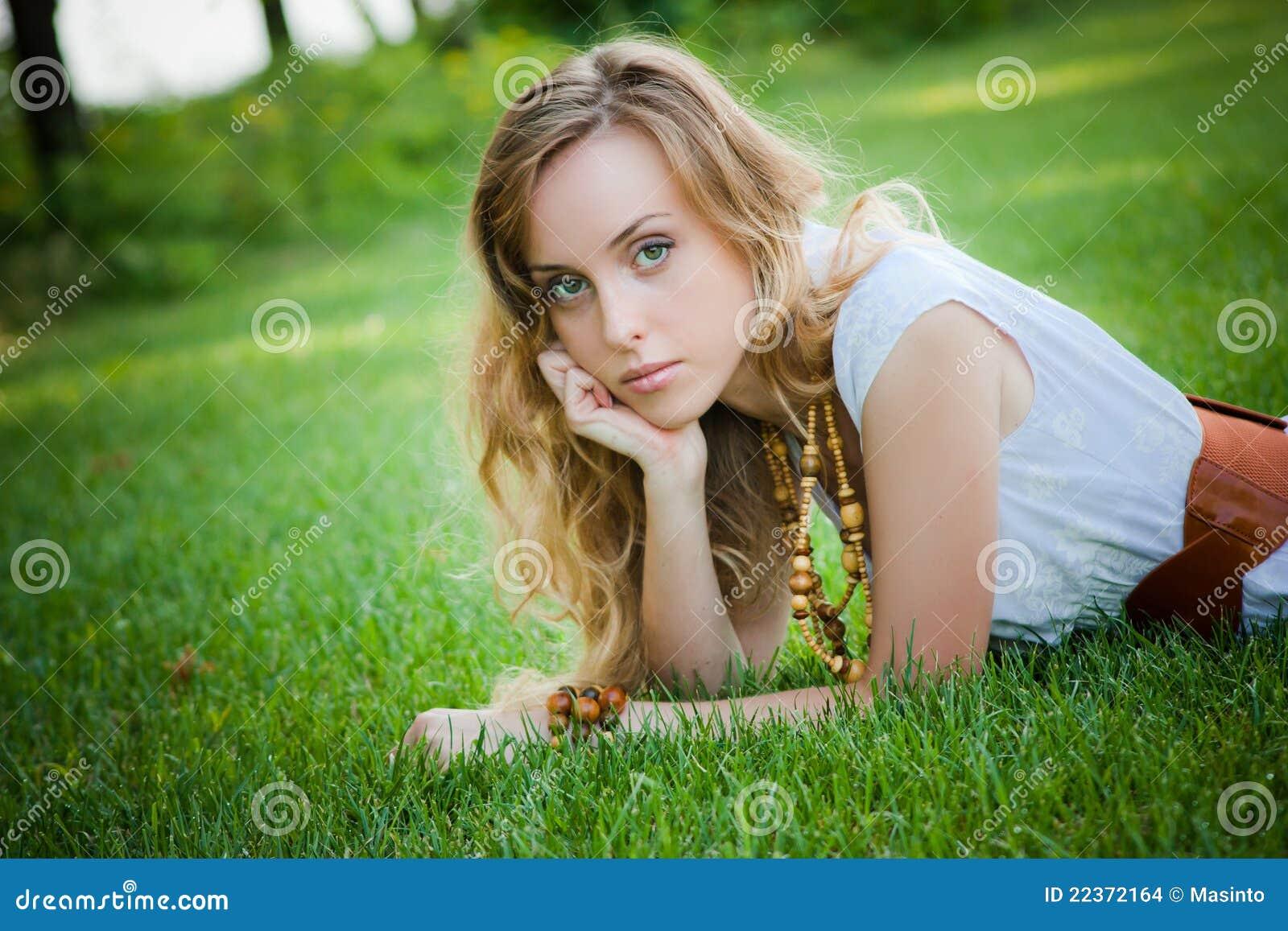 美丽的女孩在草位于