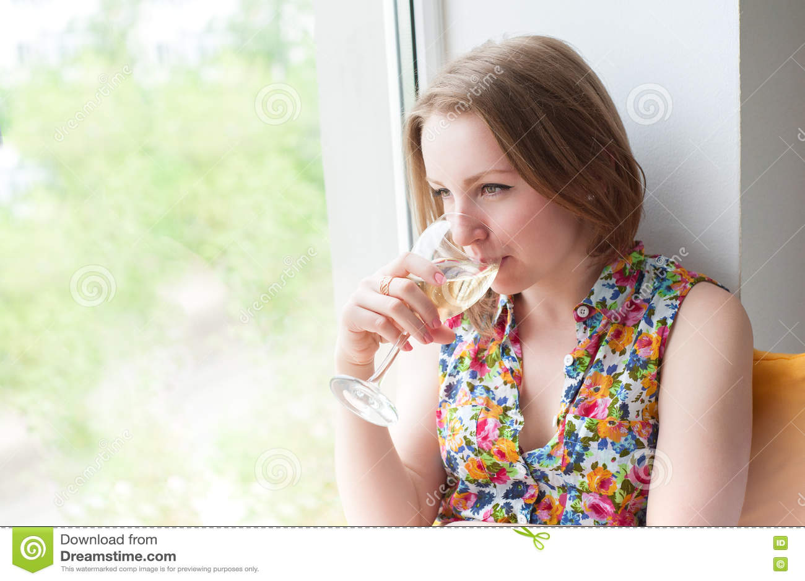 美丽的女孩坐与电话的窗口