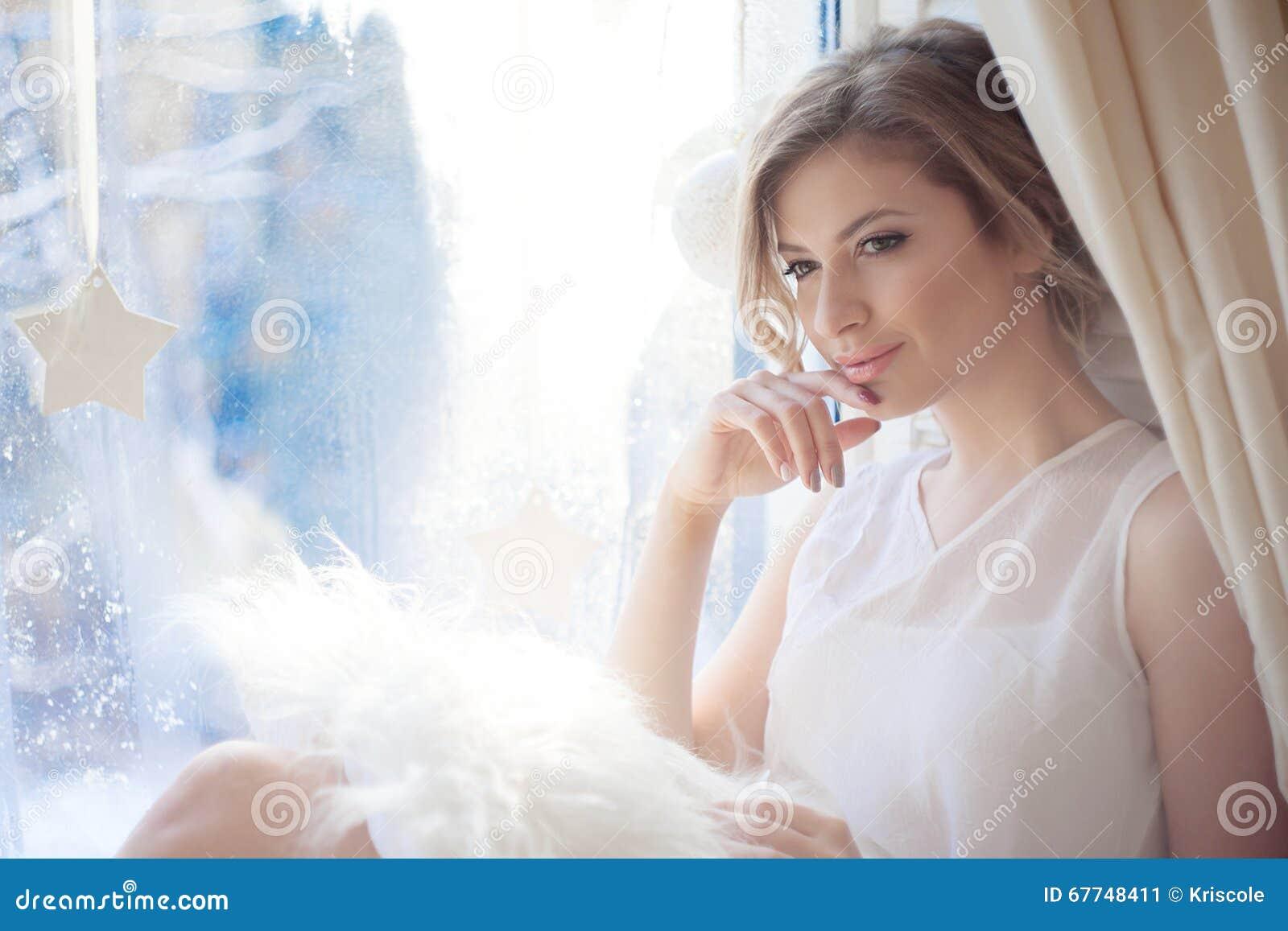 年轻美丽的女孩坐窗台,看窗口,早晨光,强光