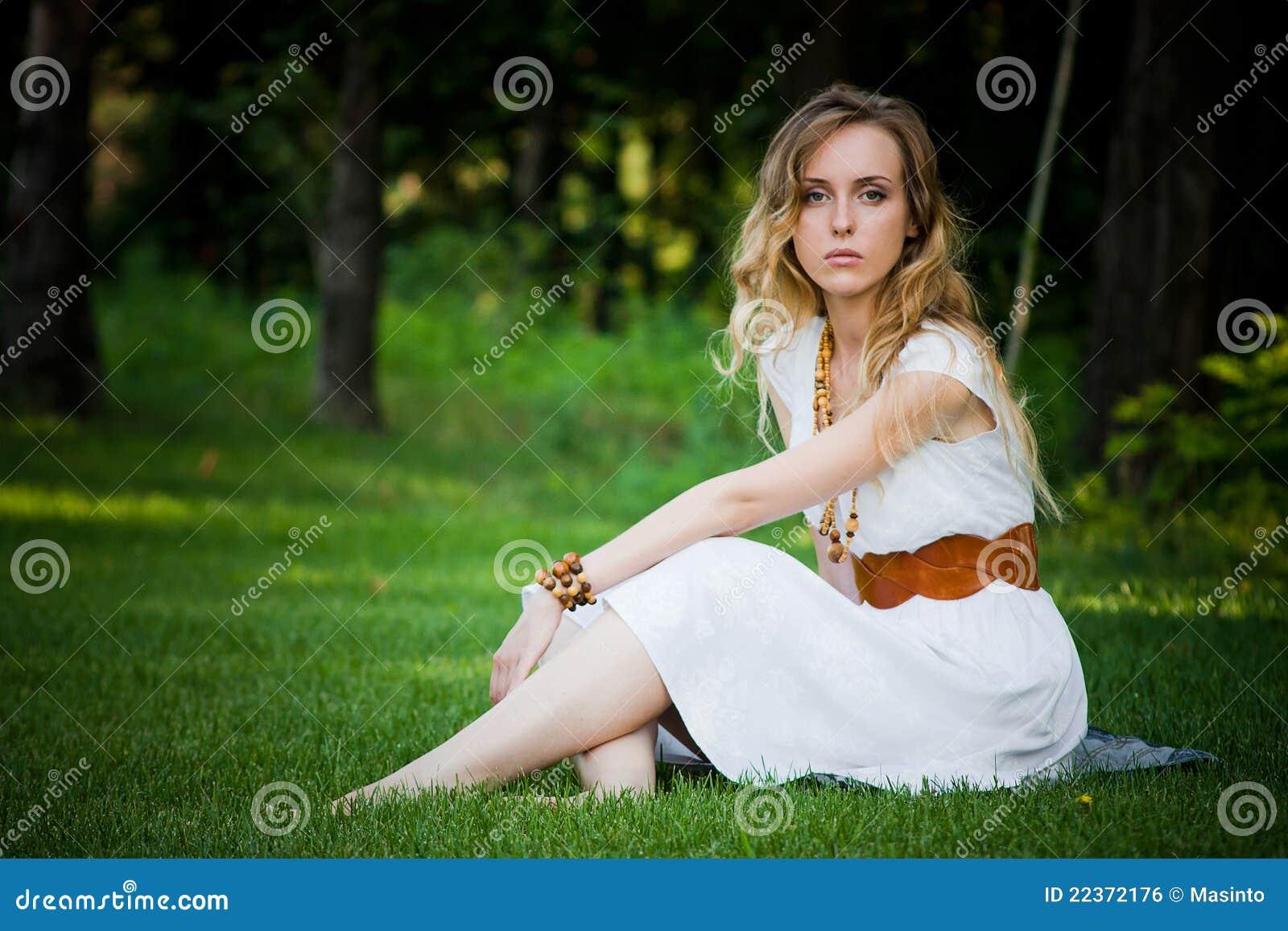 美丽的女孩坐草