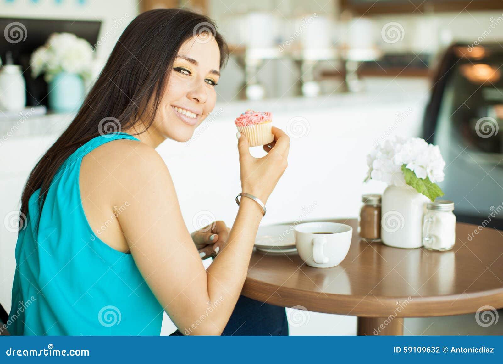美丽的女孩用咖啡和杯形蛋糕