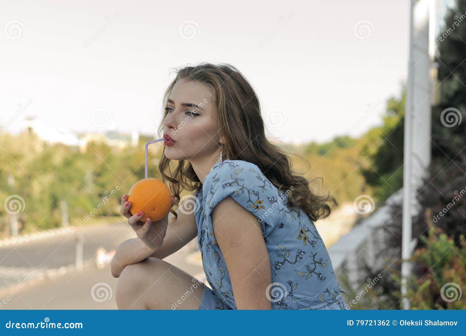 美丽的女孩通过从桔子的秸杆喝汁液