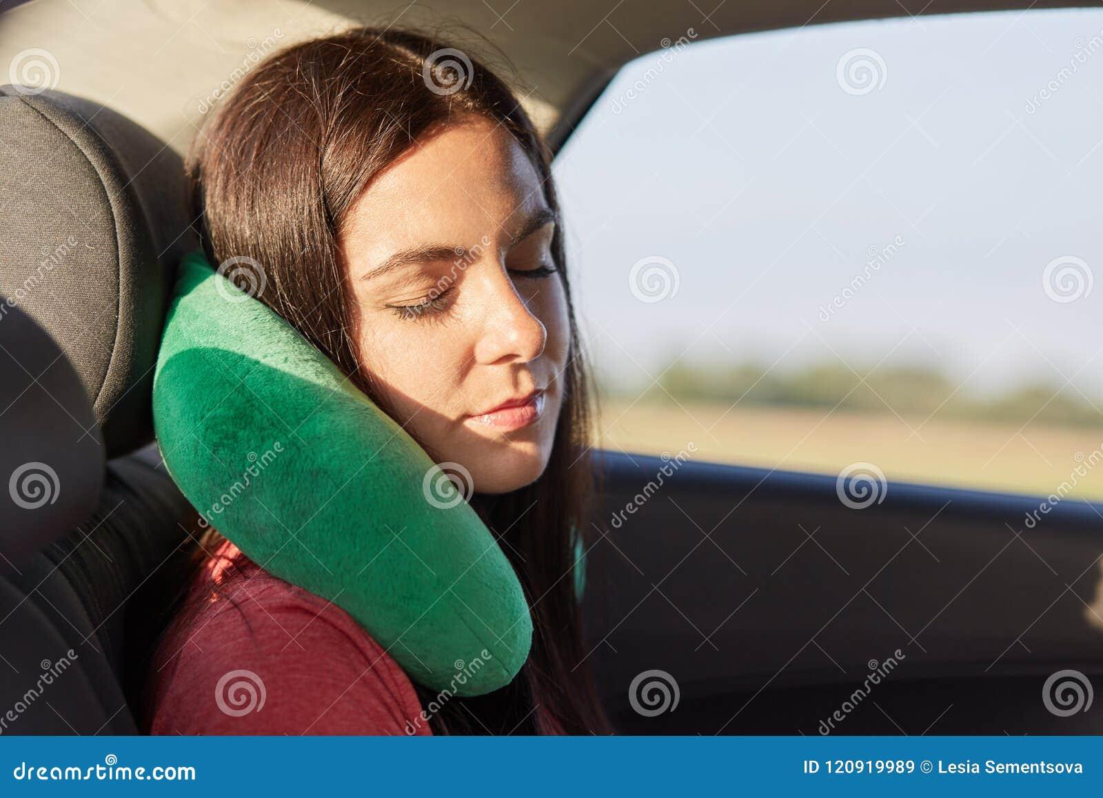美丽的女性为睡觉使用脖子枕头在汽车,有在长途, trries的放松的旅行,感觉在脖子的痛苦的
