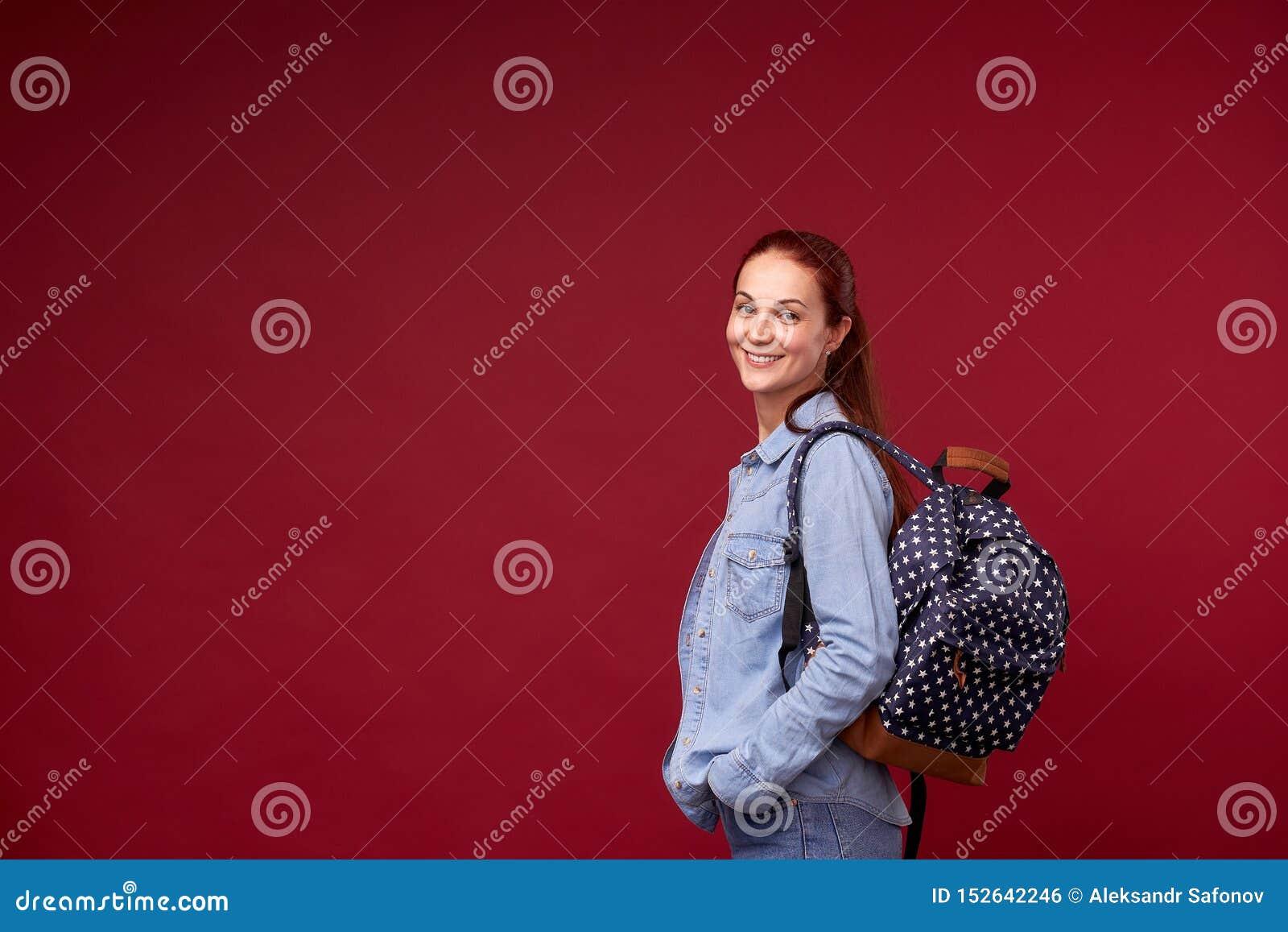 美丽的女生 牛仔裤和一个背包的一名正面红发学生在她的在红色背景立场的肩膀后和