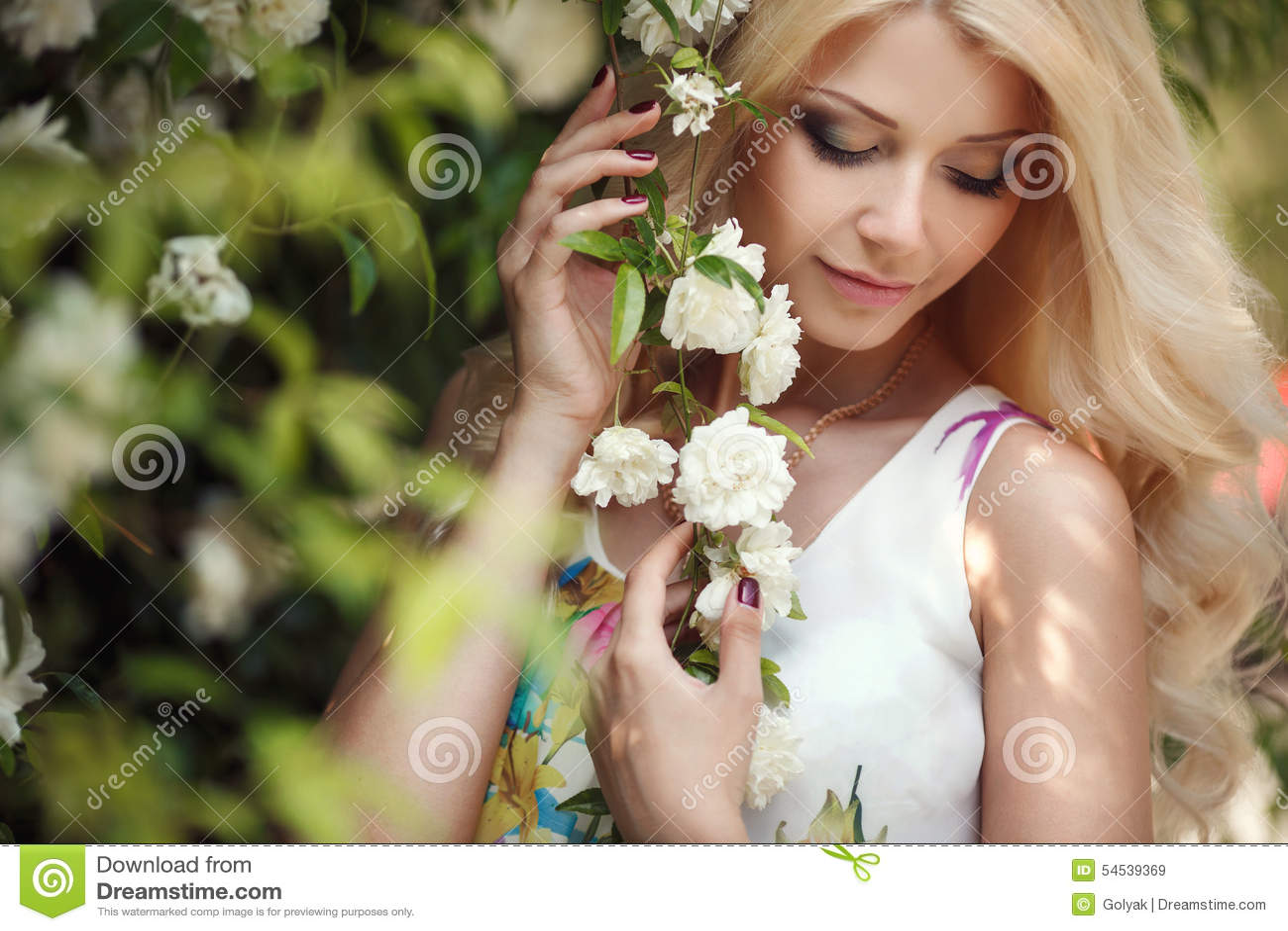 美丽的妇女在布什开花的玫瑰附近的公园
