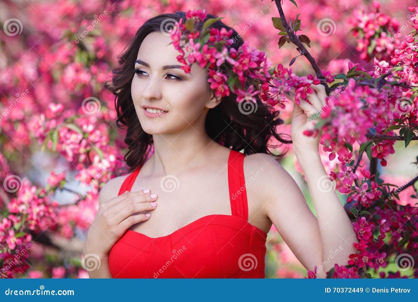 美丽的妇女在有桃红色花的一个公园