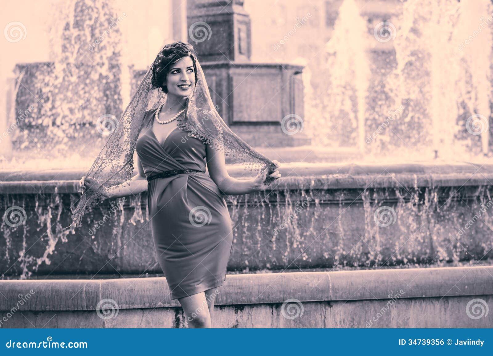 美丽的妇女在都市背景中。葡萄酒样式