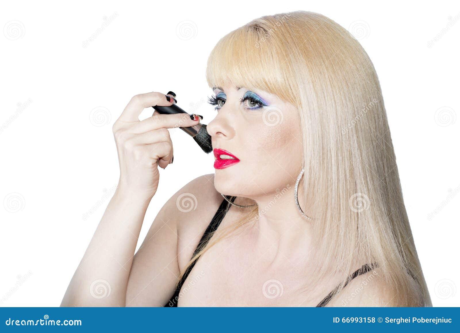 美丽的妇女在面孔上把刷子放构成