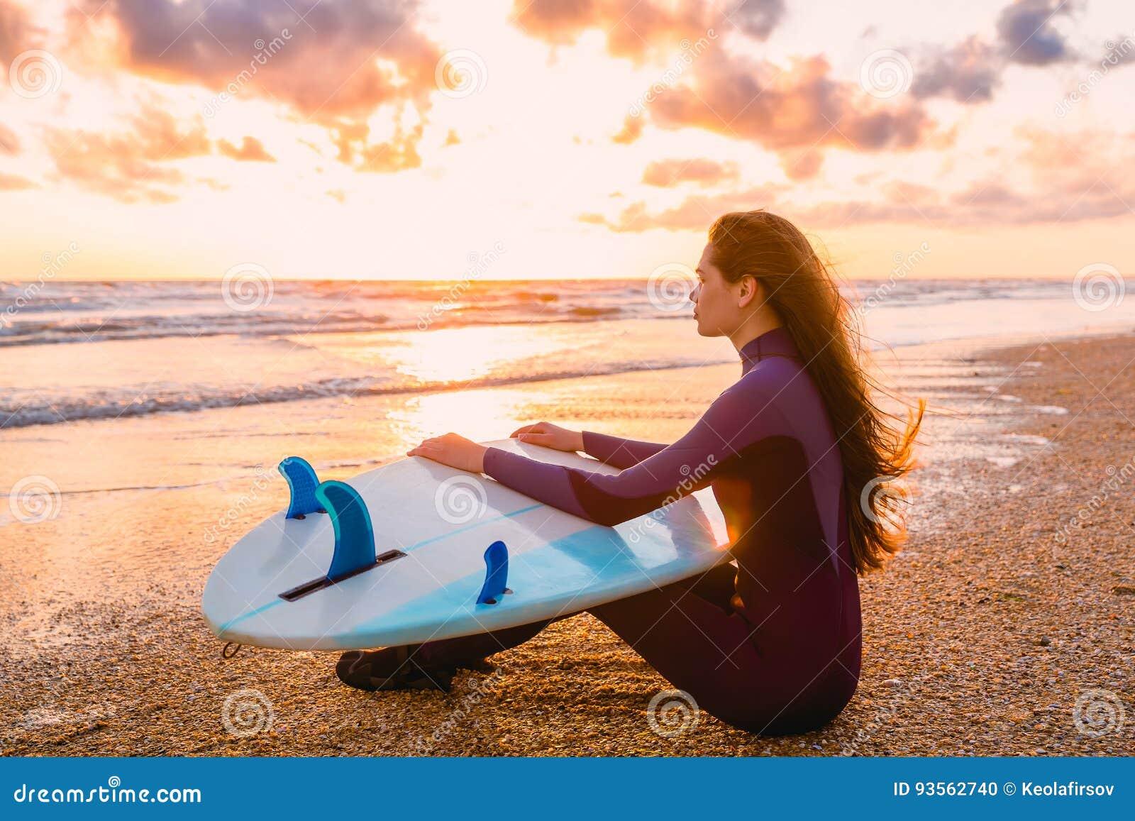 年轻美丽的妇女坐海滩 冲浪有冲浪板的女孩在海滩在日落或日出 冲浪者和海洋