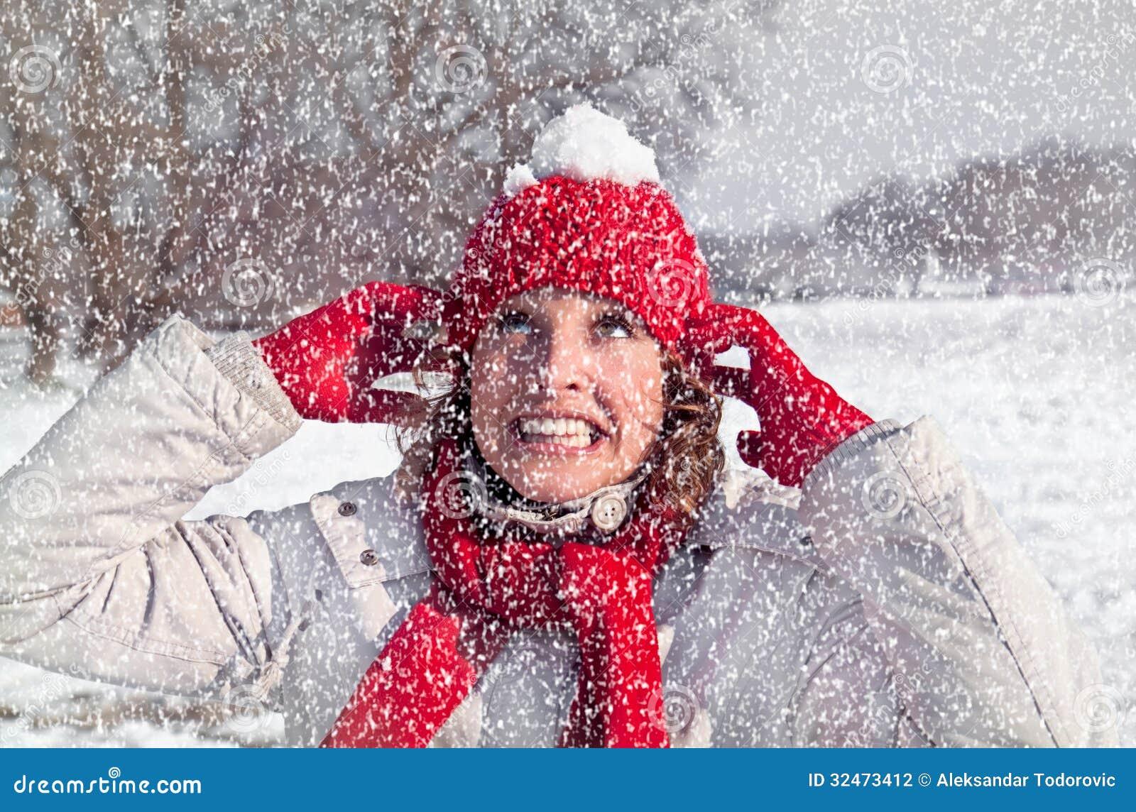 美丽的妇女有在一个红色盖帽的一个雪球
