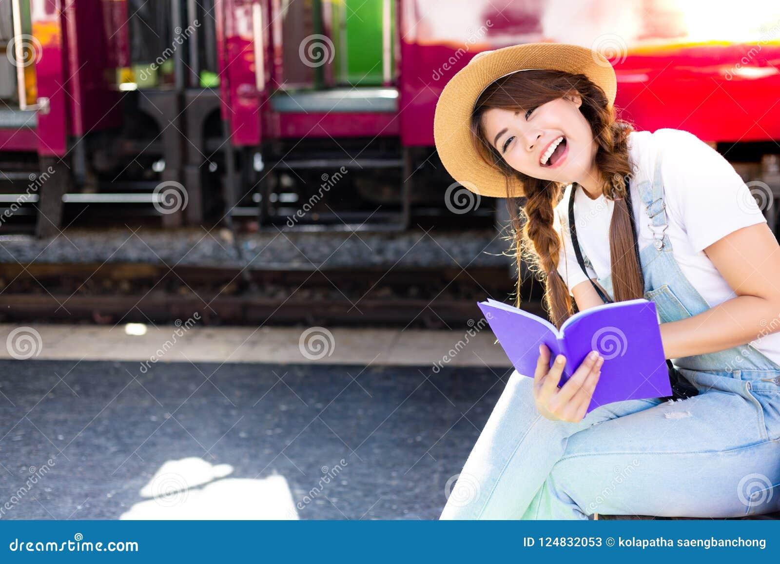 美丽的妇女读看起来的旅行指南旅游