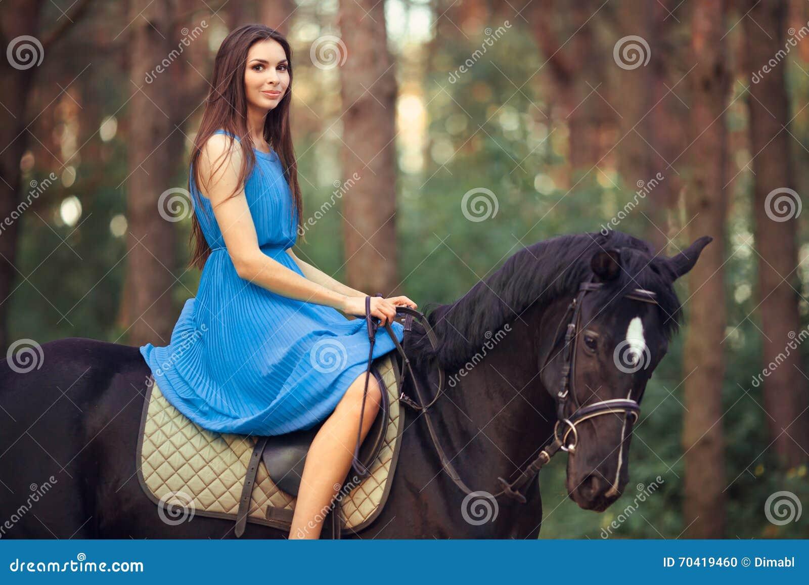 美丽的妇女骑乘马在森林里