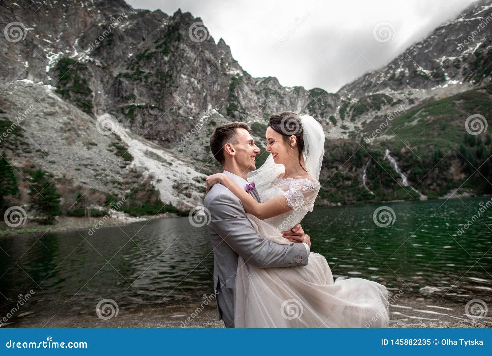 美丽的婚姻的photosession 新郎盘旋他的年轻新娘,湖Morskie Oko的岸的 ??