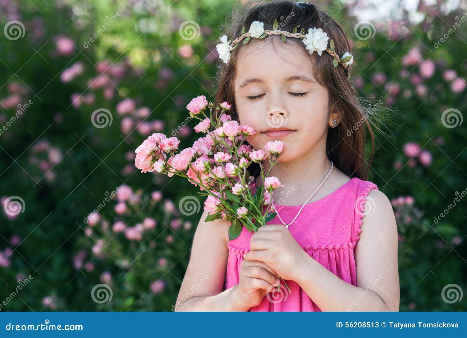 美丽的小女孩画象有玫瑰的开花