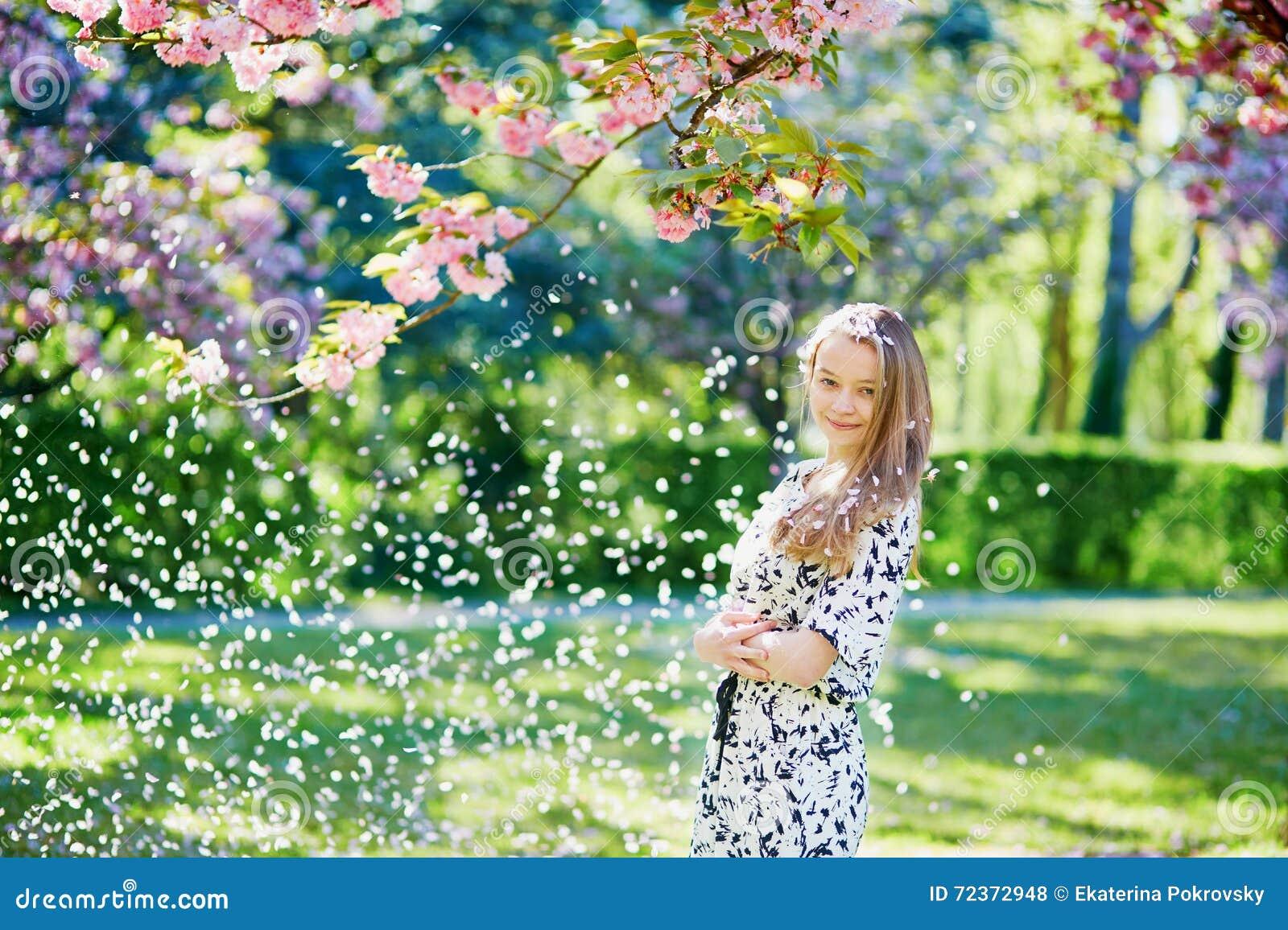 美丽的少妇在开花的春天公园