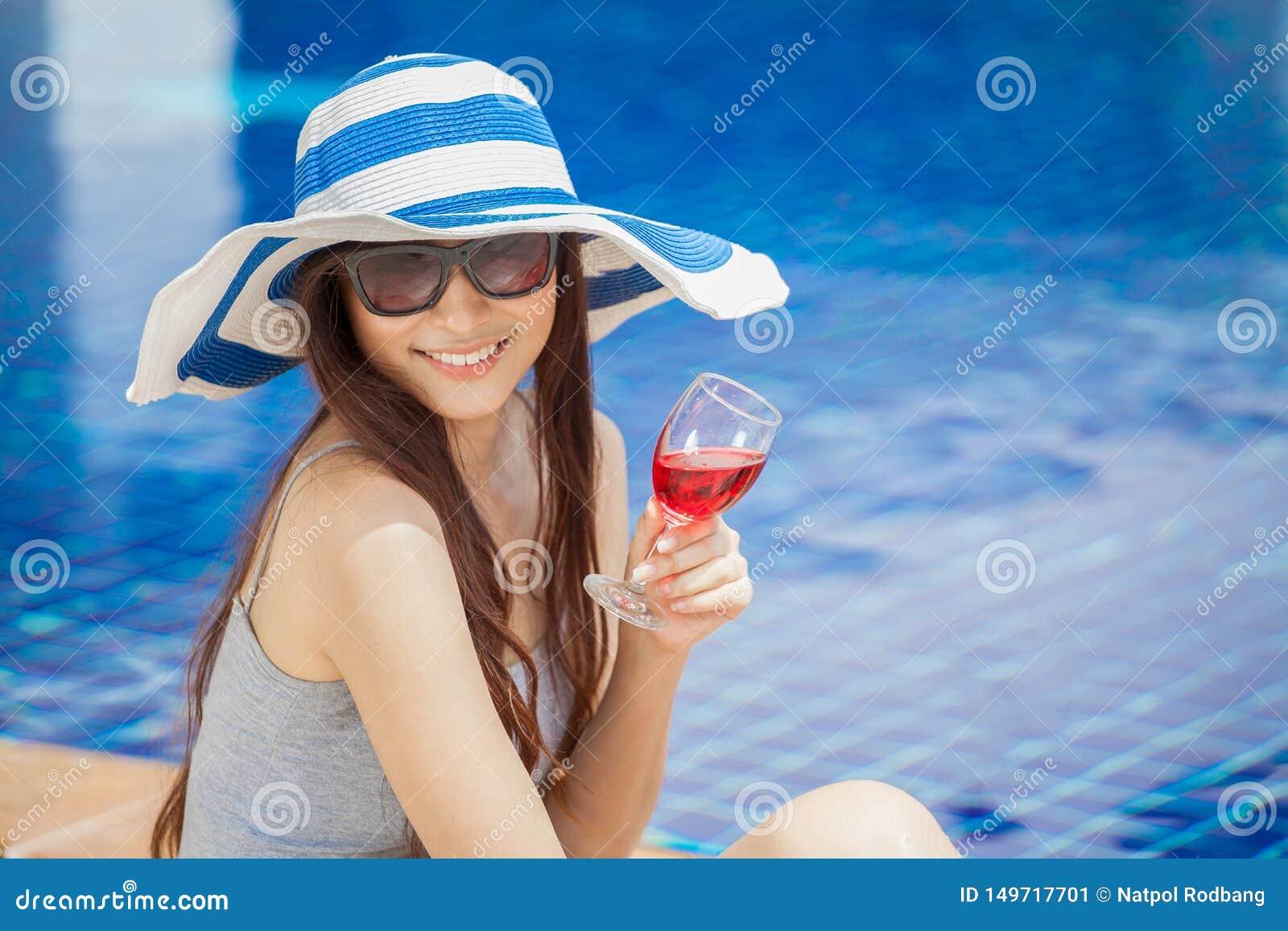 美丽的年轻亚裔妇女用在夏天党的饮料在游泳场附近 大帽子和玻璃放松的愉快的女孩