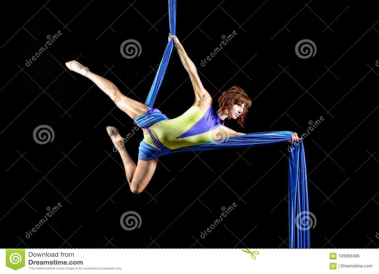 美丽的年轻人,运动性感的有红头发人的妇女专业空中马戏艺术家在黄色服装在天空中的摆在对角线,