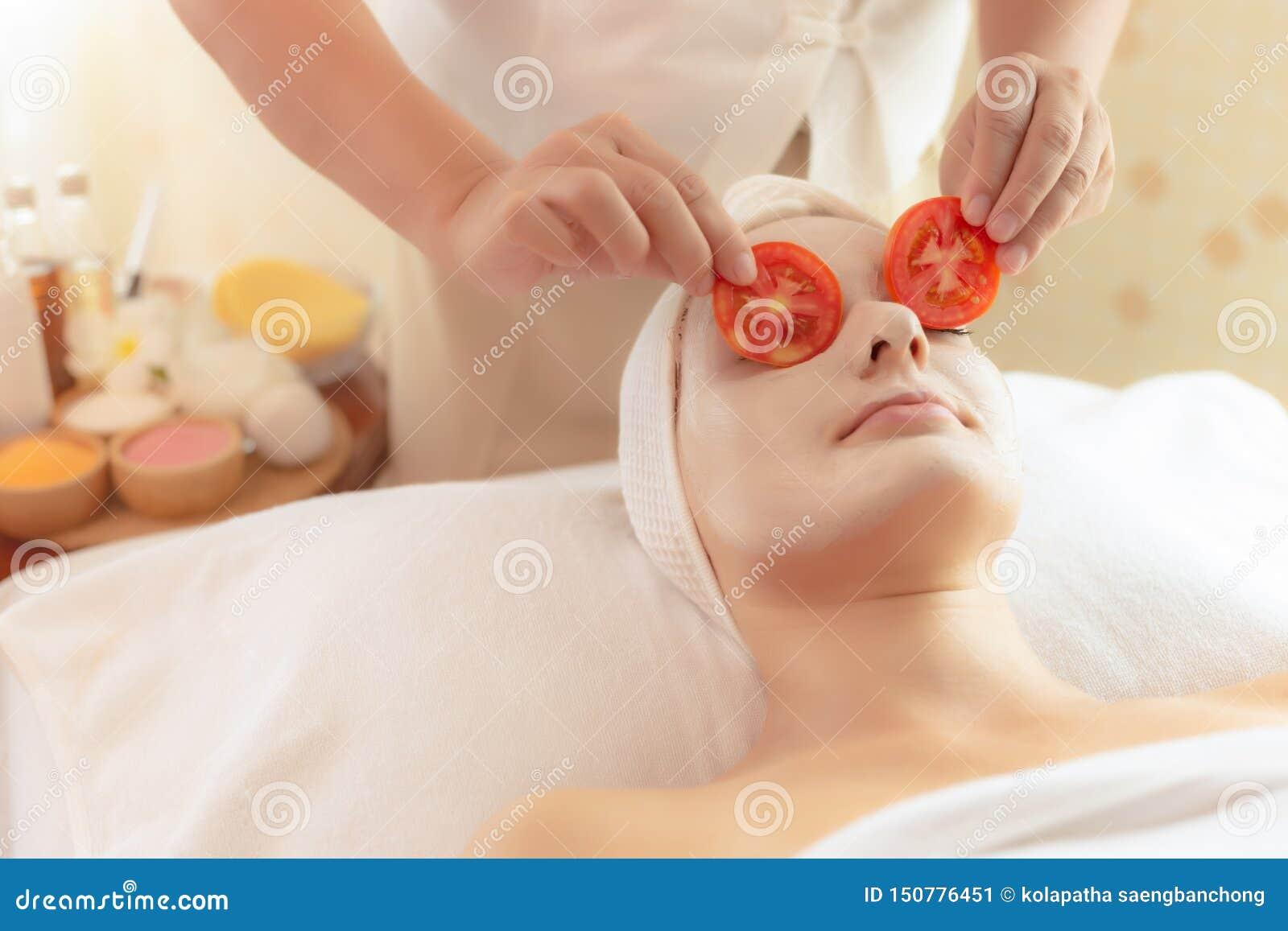 美丽的年轻女人在温泉床上躺下在温泉屋子里在温泉沙龙 女按摩师在使的顾客眼睛上把蕃茄切片放明亮