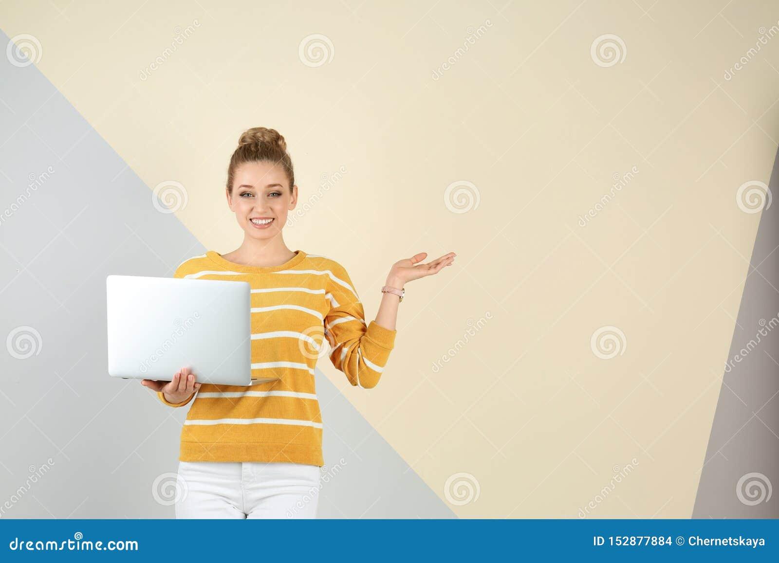 美丽的年轻女人画象有膝上型计算机的在颜色背景