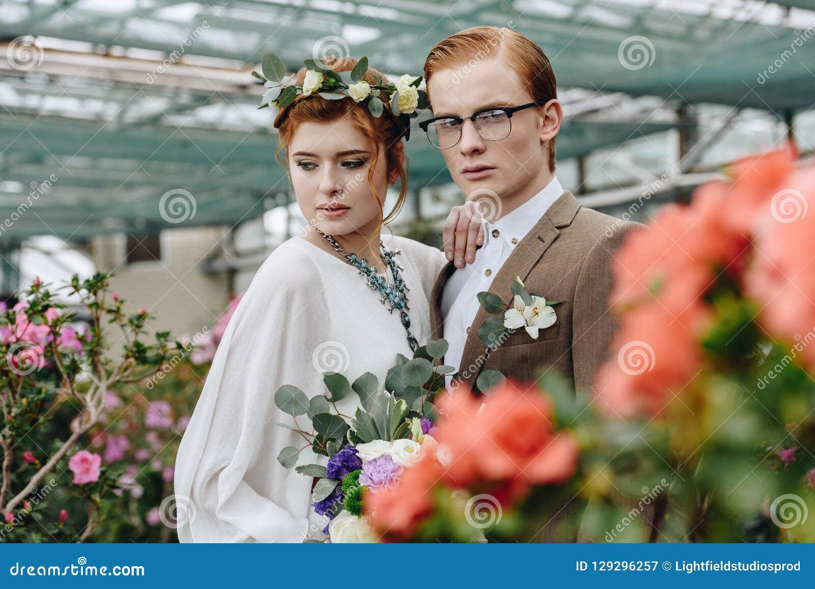 美丽的年轻新郎和新娘有一起站立在植物的婚礼花束的