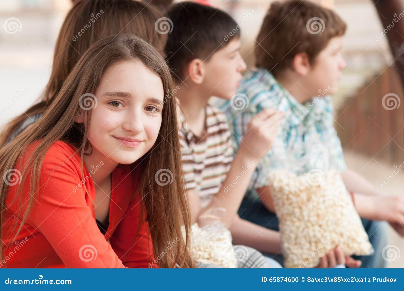 美丽的微笑的十几岁的女孩画象有她的朋友的