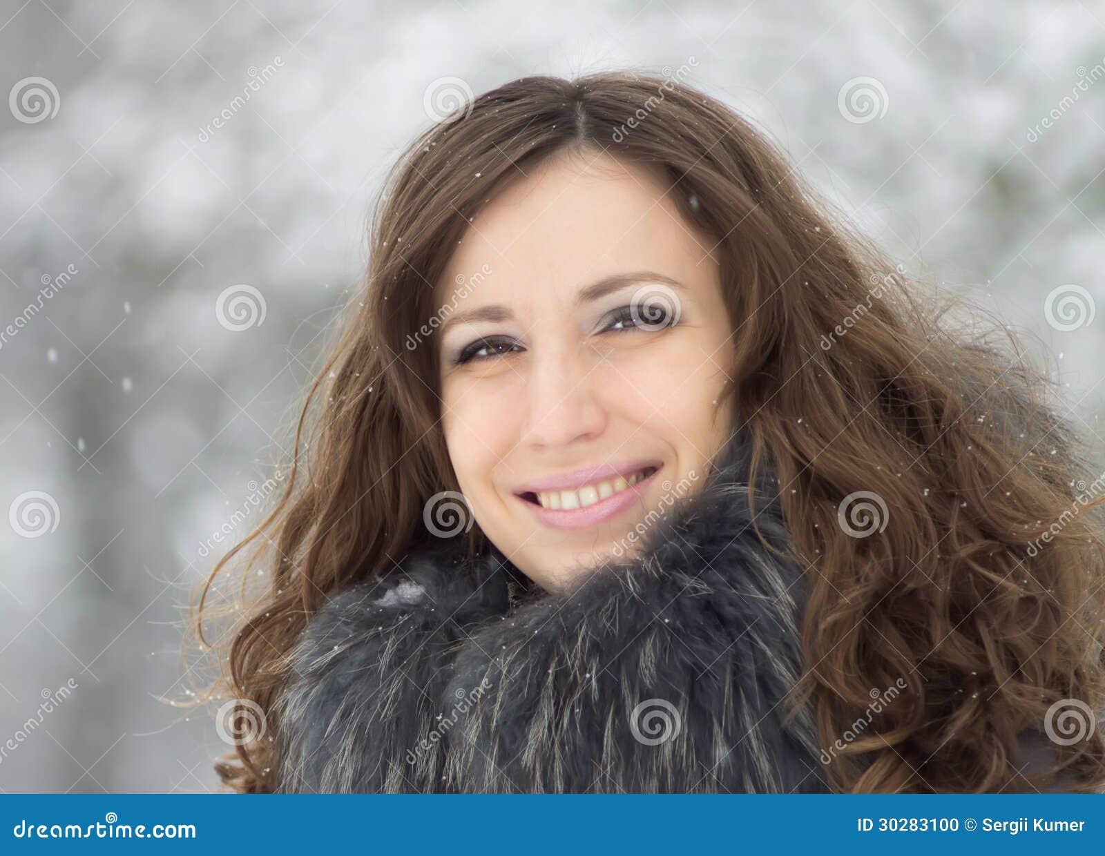 美丽的微笑的少妇在多雪的冬天停放