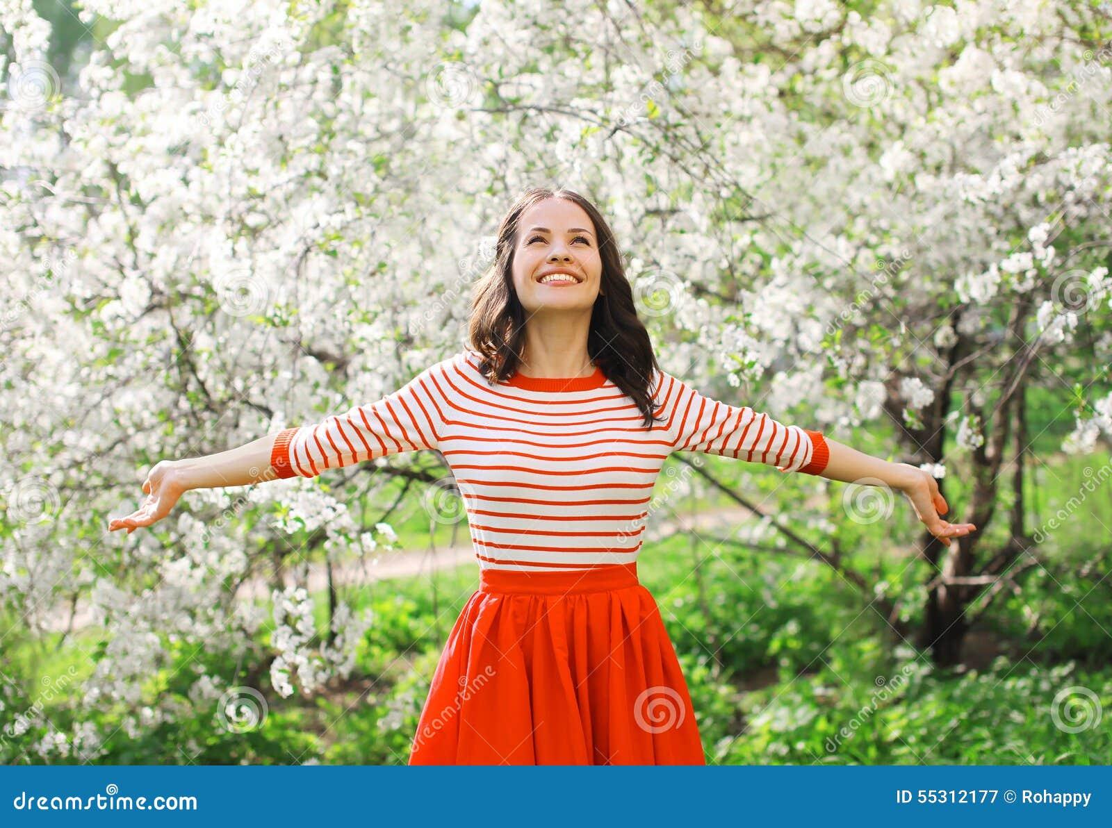 美丽的愉快的少妇在开花的春天的享用气味