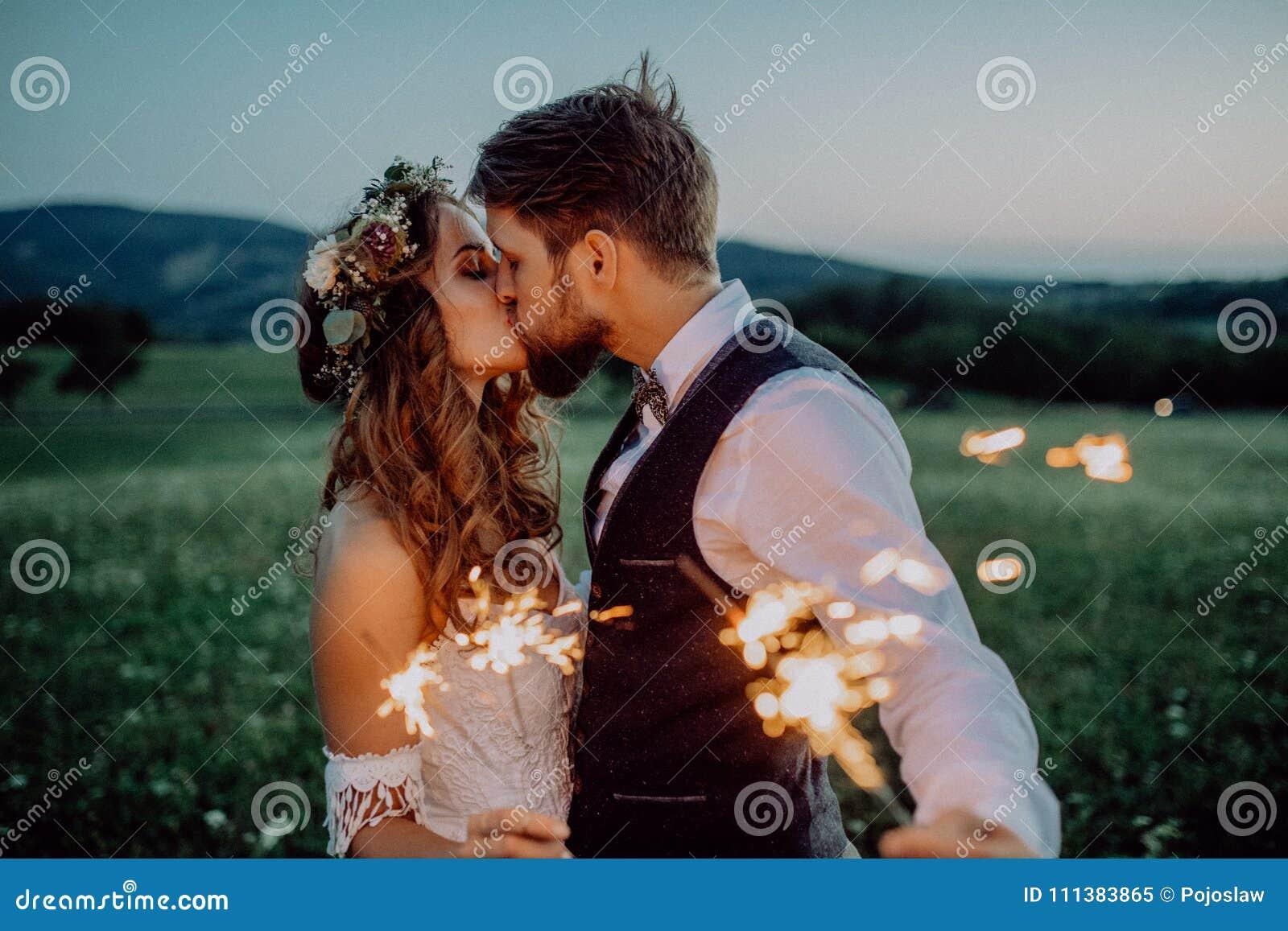 美丽的新娘和新郎与闪烁发光物在草甸