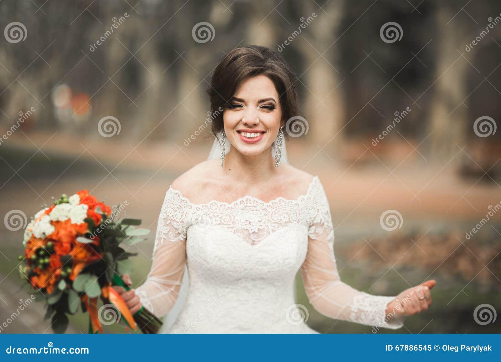 美丽的新娘在公园在她的与花束的婚礼之日