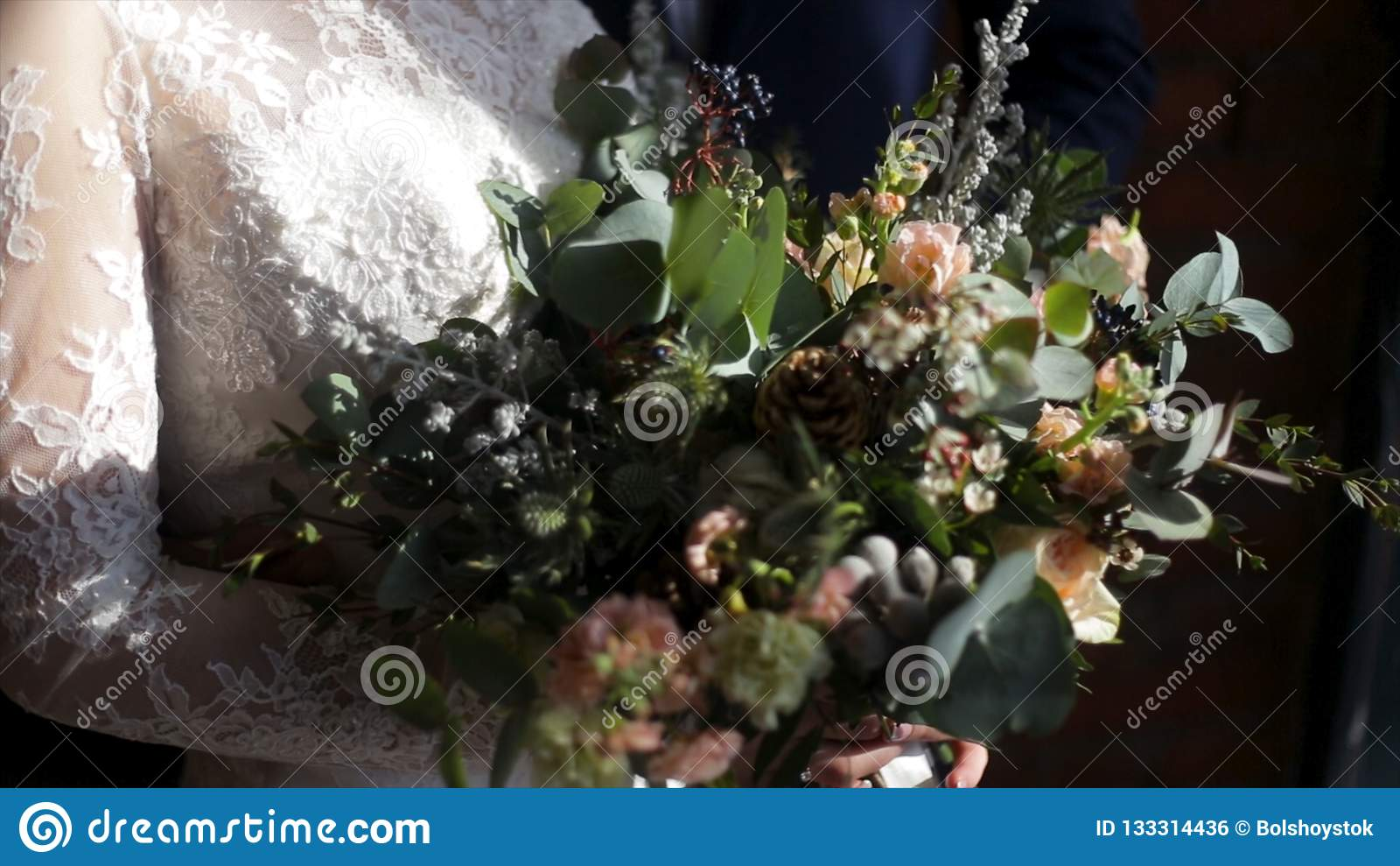 美丽的新娘花束在年轻新娘的手上在白色婚礼礼服穿戴了 接触婚礼花束的新娘手