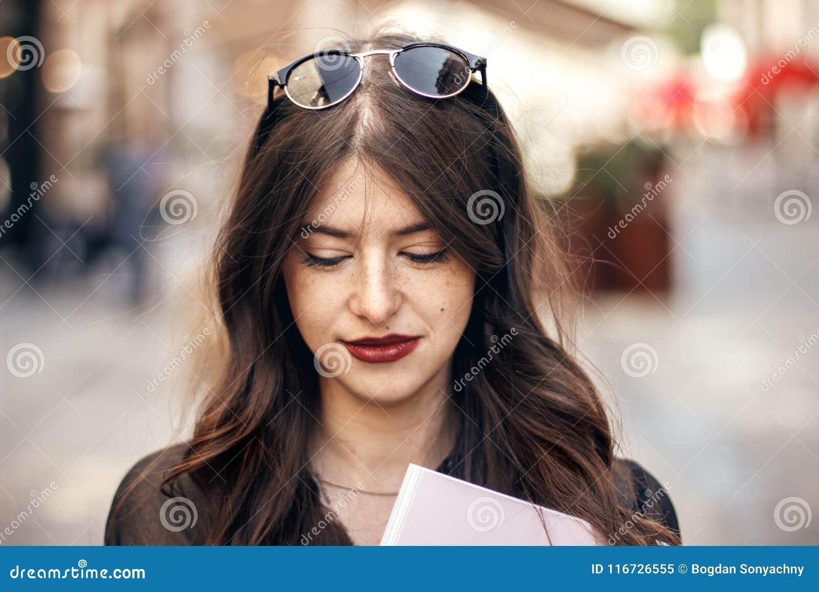 美丽的时髦的行家女孩微笑在晴朗的城市街道的, hol
