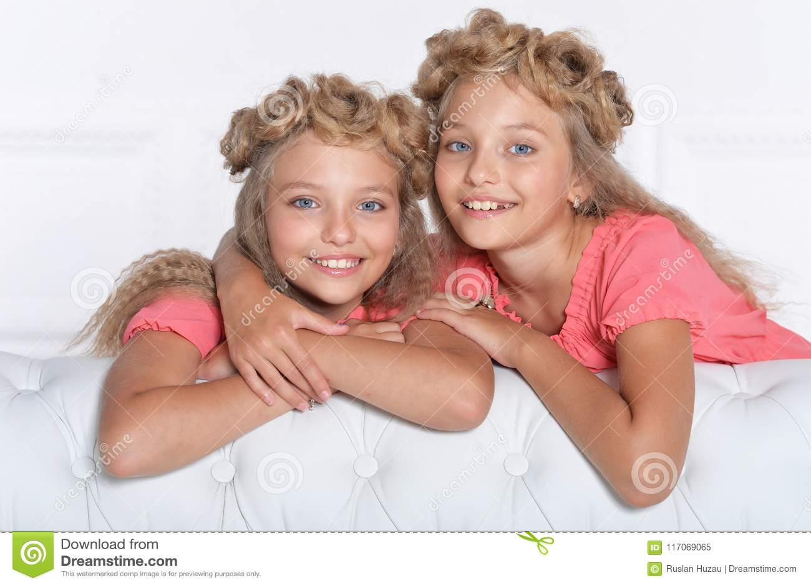 美丽的桃红色礼服的两个可爱的双姐妹