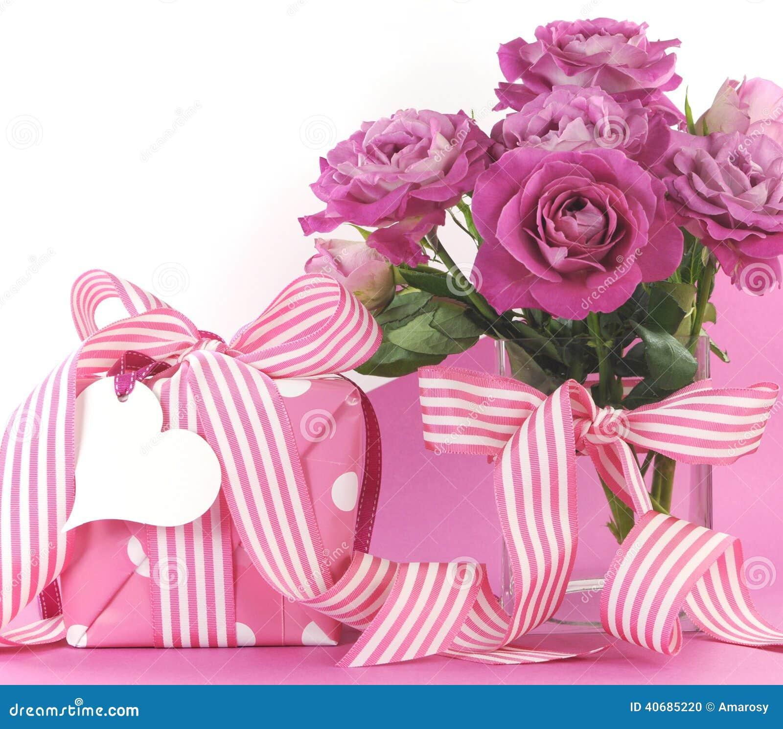 美丽的桃红色礼物和玫瑰在桃红色和白色背景与拷贝空间