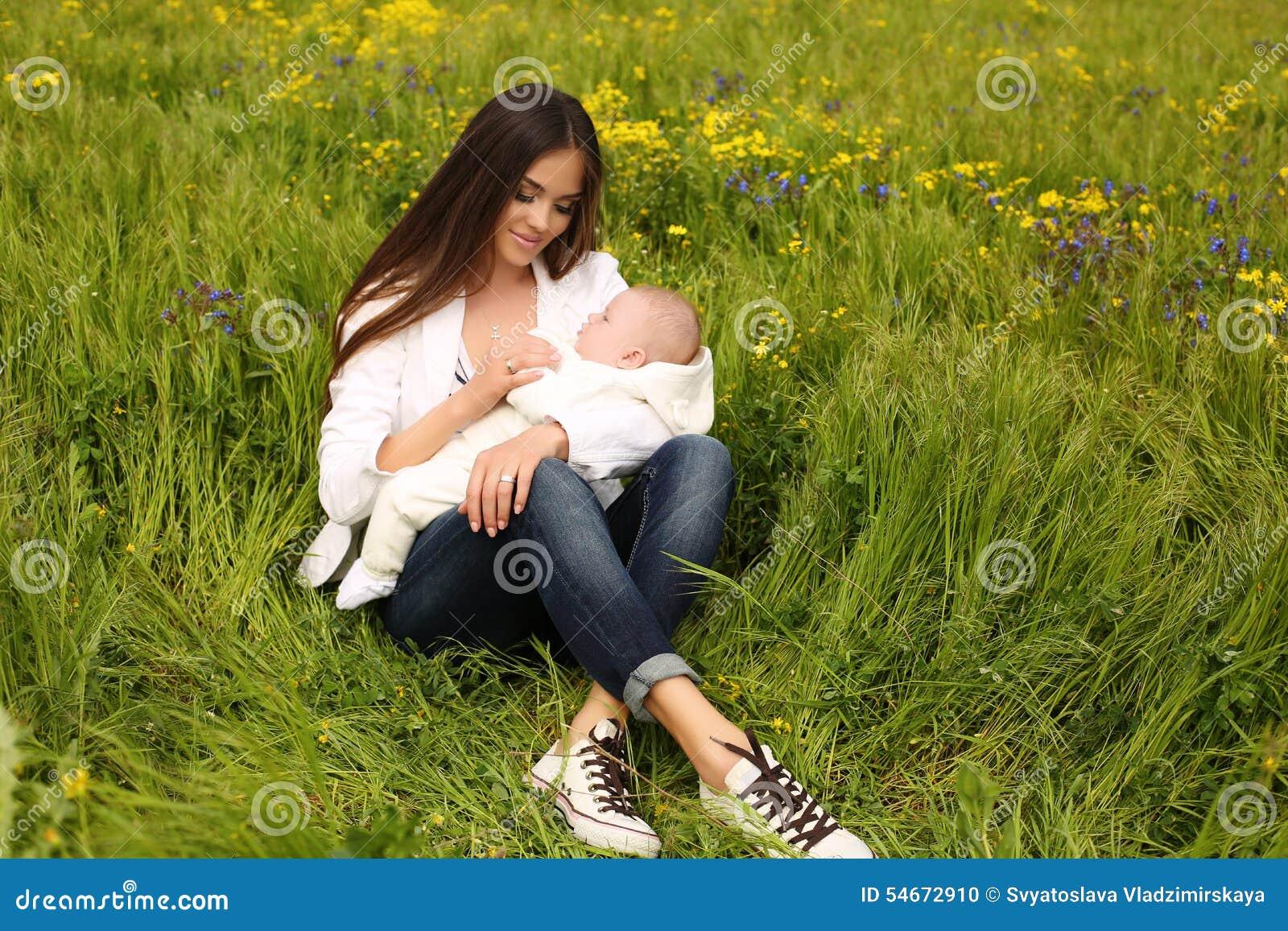 美丽的母亲获得与她的小逗人喜爱的婴孩的乐趣在夏天庭院