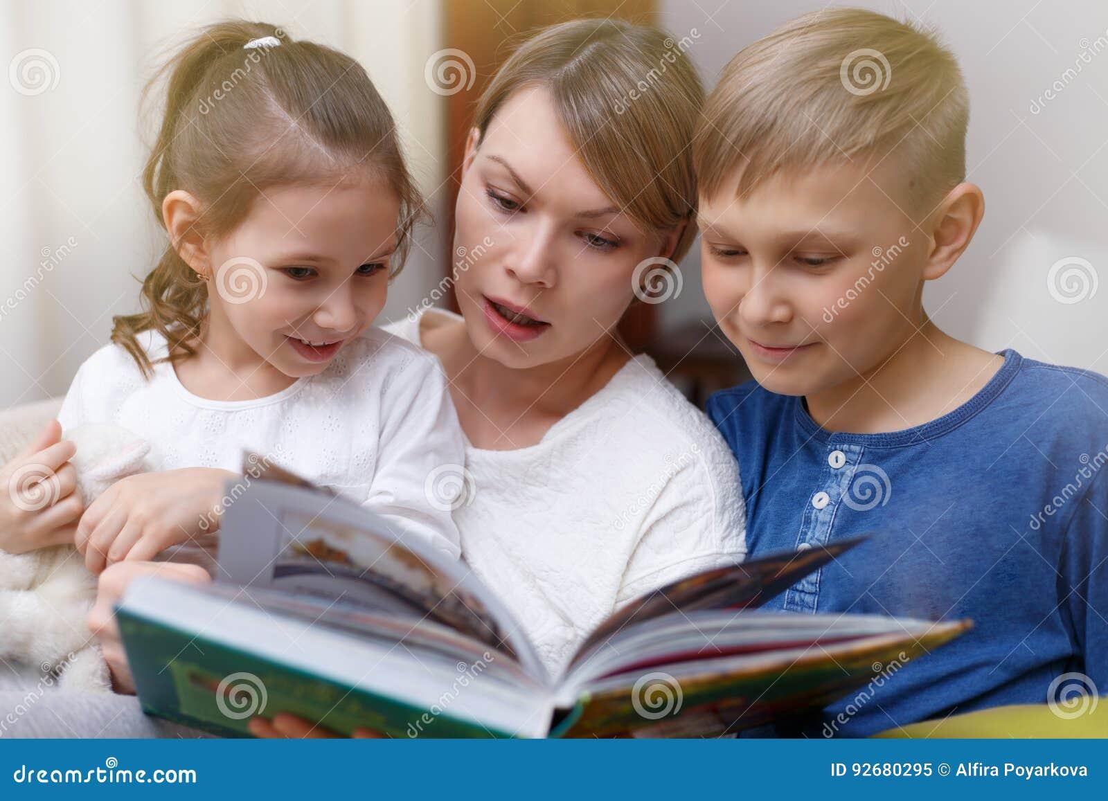 美丽的母亲读一本书给她的幼儿 姐妹和兄弟听故事