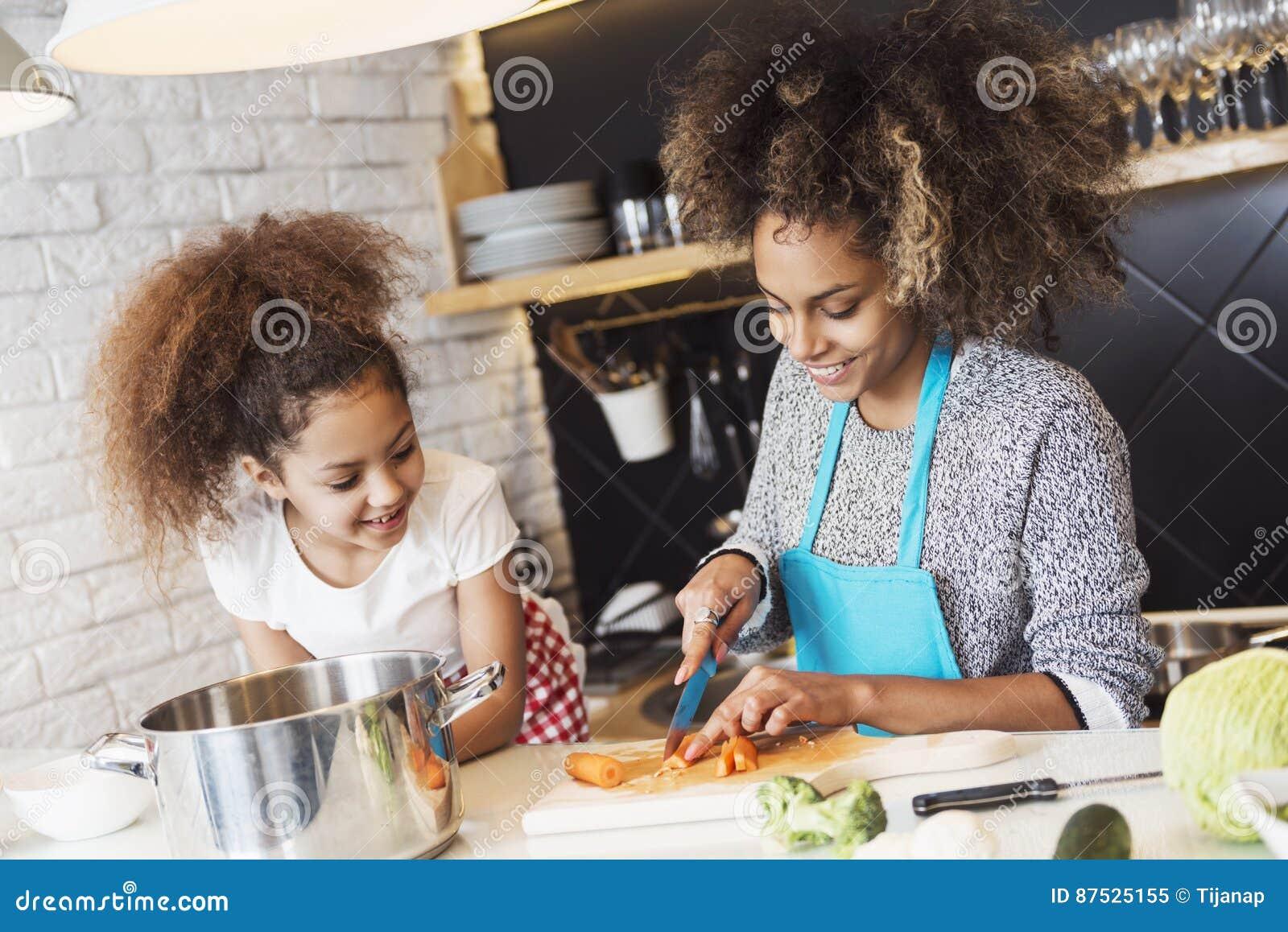 美丽的烹调在厨房里的妇女和她的女儿
