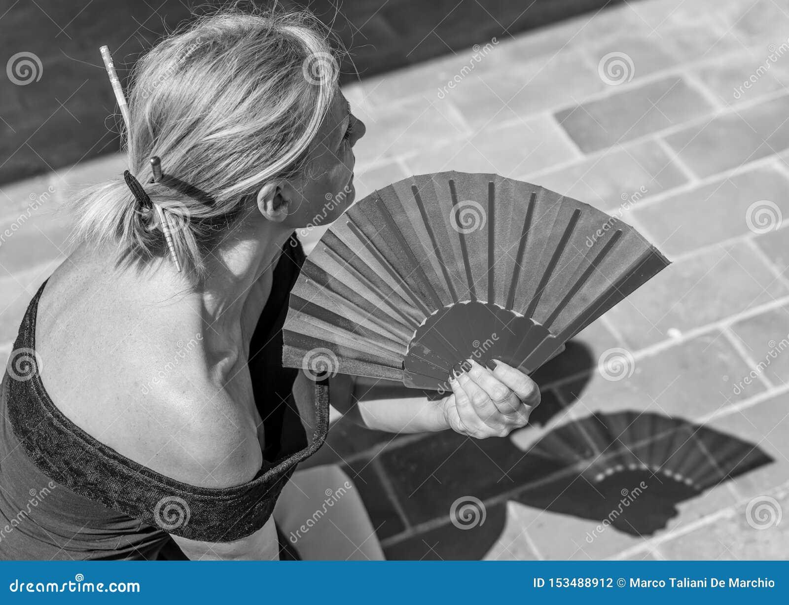 美丽的白种人妇女在一个热的夏日使用一个手爱好者变冷静