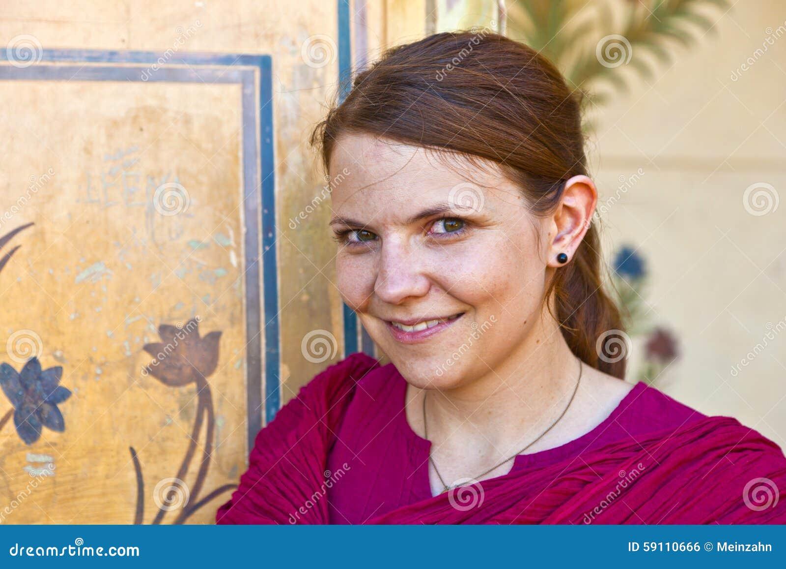 美丽的白种人妇女画象有老墙壁的作为backgroun