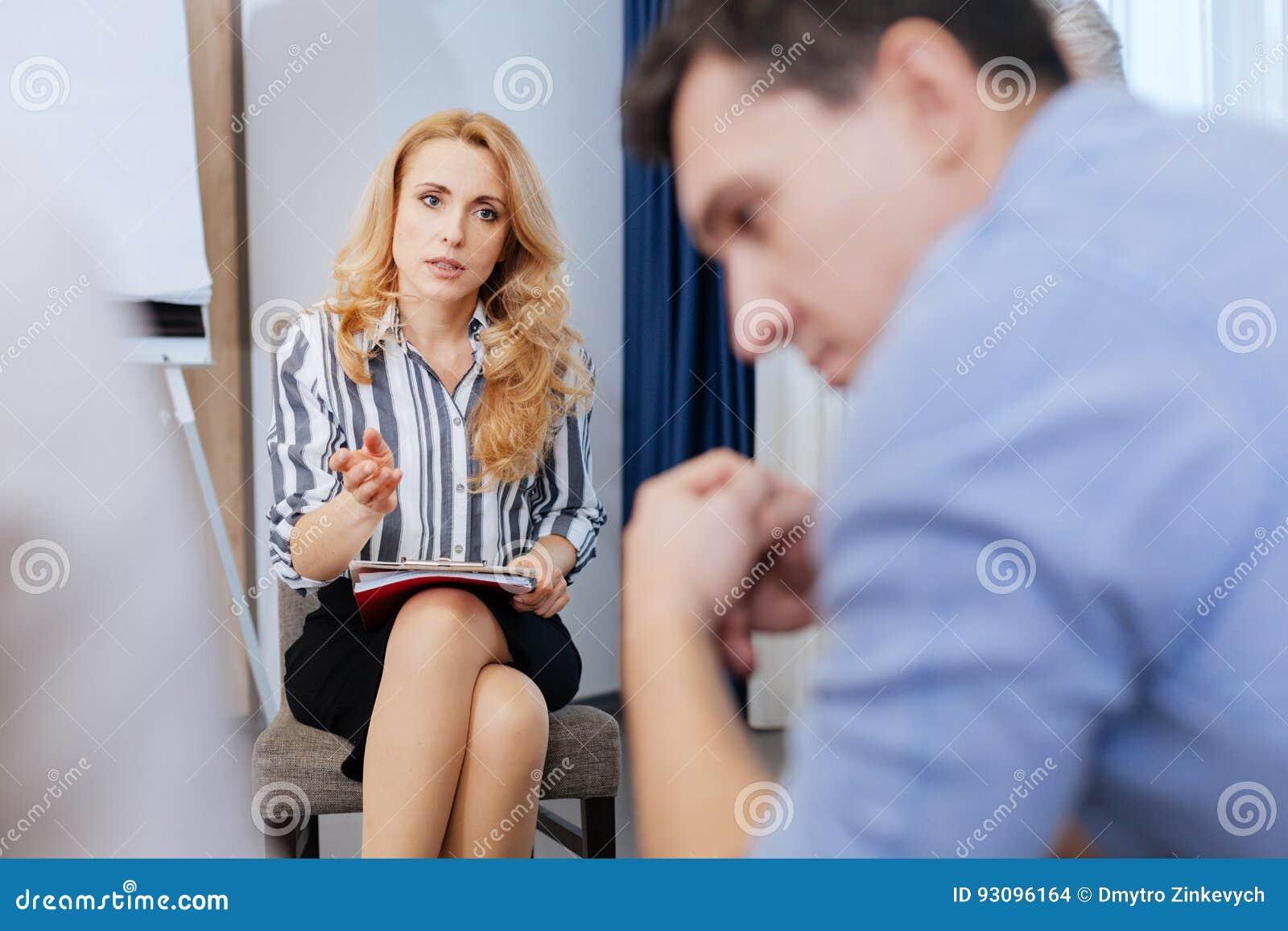 美丽的白肤金发的妇女谈话与她的患者