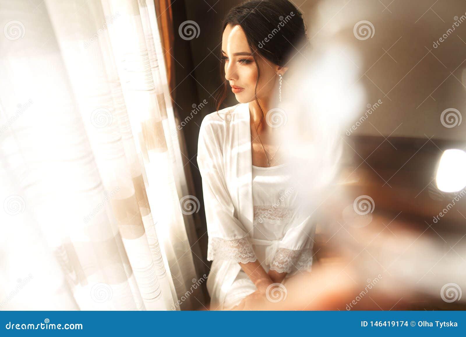 美丽的礼服的新娘坐椅子户内在象在家的白色演播室内部 时髦婚姻的样式射击