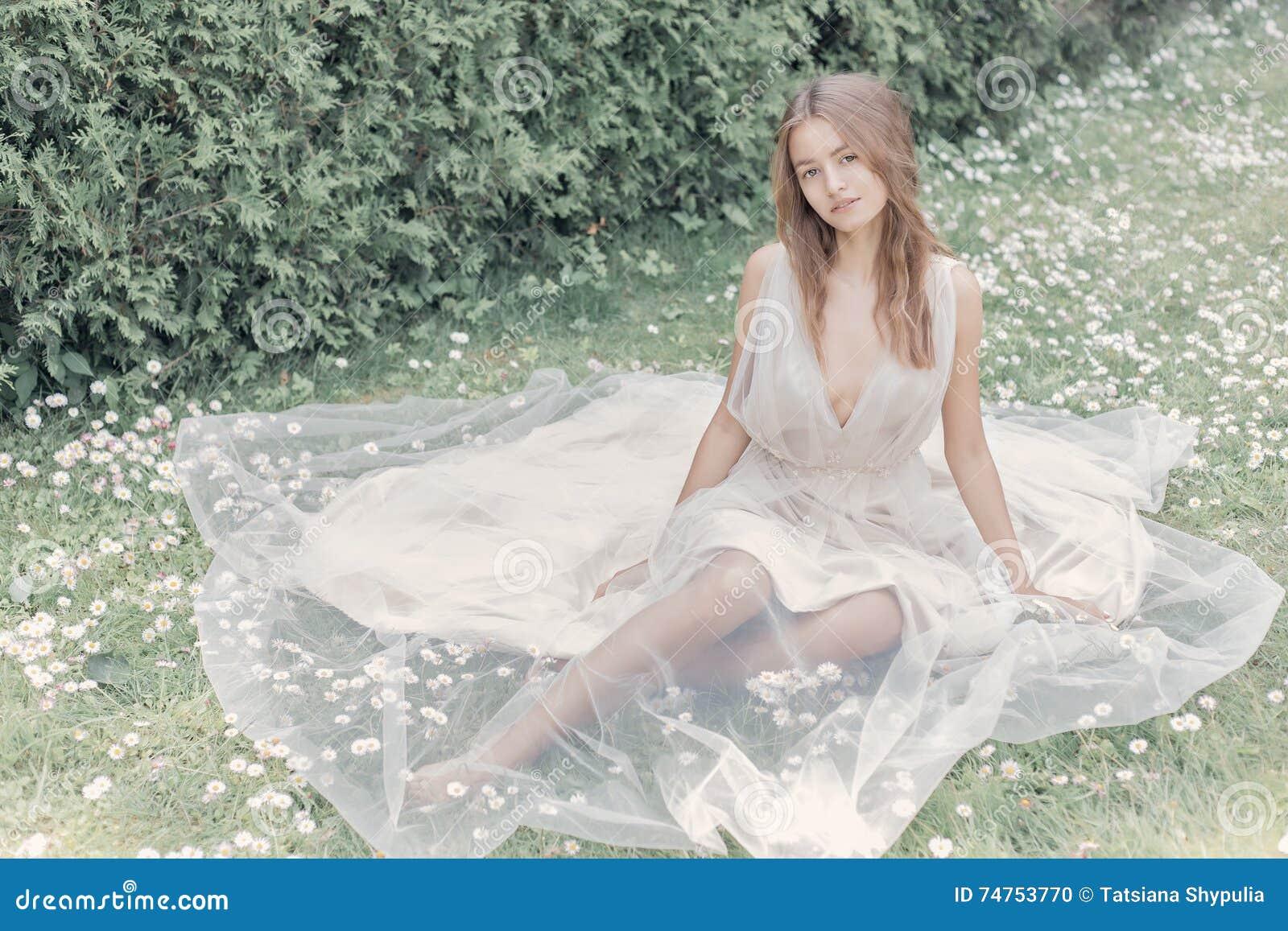 美丽的精美一套轻的米黄婚礼礼服的新娘性感的女孩在庭院明亮的晴朗的温暖的天走