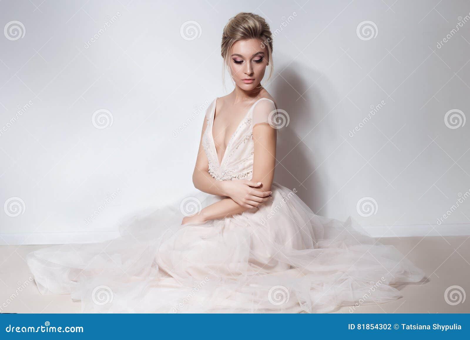 美丽的精美软的桃红色skazachno婚礼礼服的新娘性感的女孩与在胸口和后面的裁减与构成和晚上h
