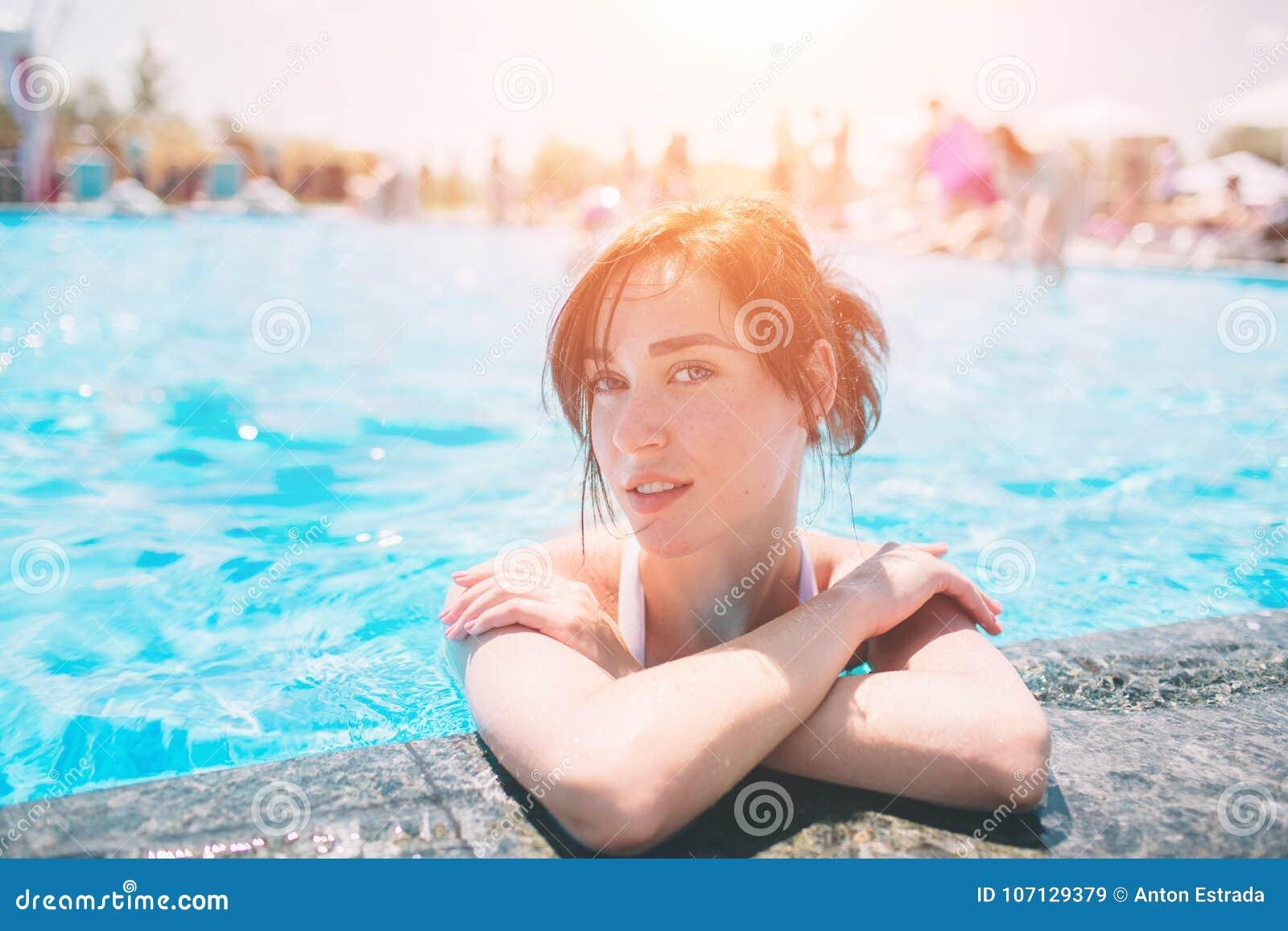 美丽的被晒黑的妇女画象放松在游泳池温泉的白色游泳衣的 热的夏日和明亮晴朗