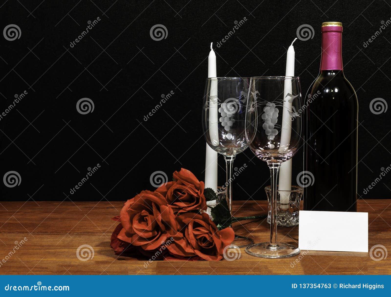 美丽的被铭刻的酒杯和瓶红酒、白色蜡烛和英国兰开斯特家族族徽在木桌上与名牌在黑暗的背景